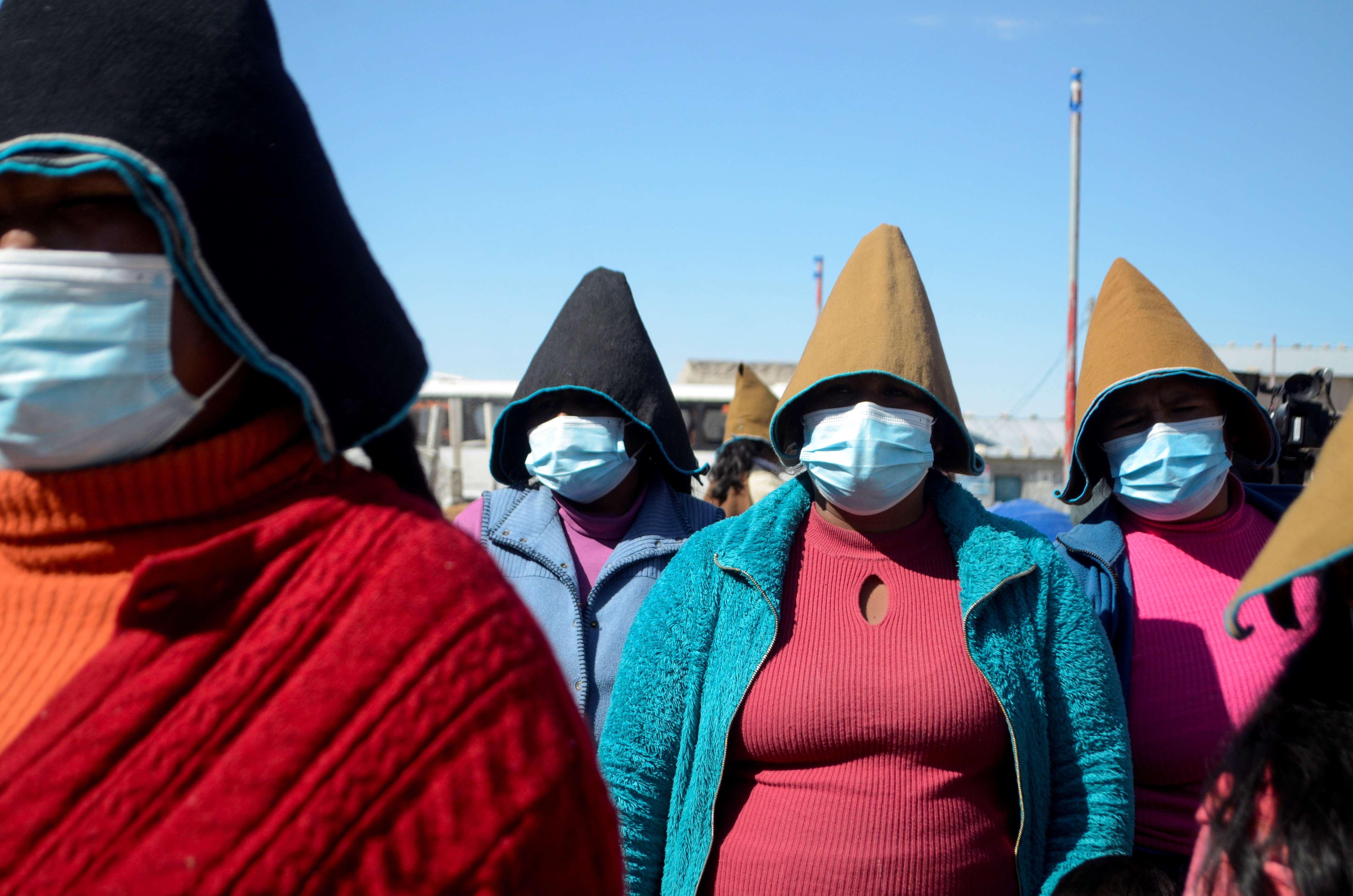 Women stand together while listening to a speaker at a health fair as others had been waiting to get vaccinated against the coronavirus disease (COVID-19), in Uru Chipaya, Bolivia July 23, 2021. REUTERS/Claudia Morales