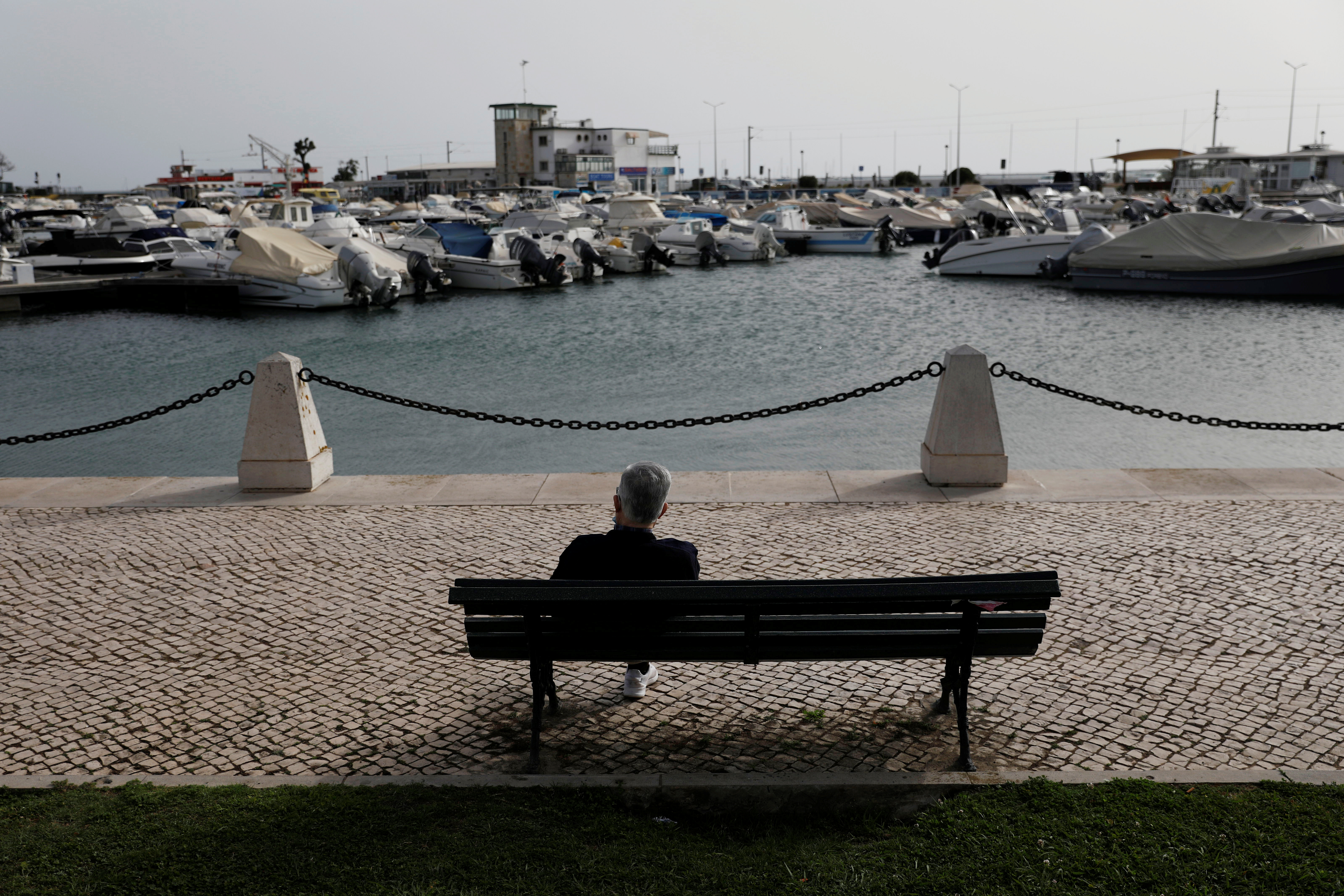 A man is seated in a bench at Faro marine, during the coronavirus disease (COVID-19) pandemic in Faro, Portugal, March 30, 2021. Picture taken March 30, 2021. REUTERS/Pedro Nunes