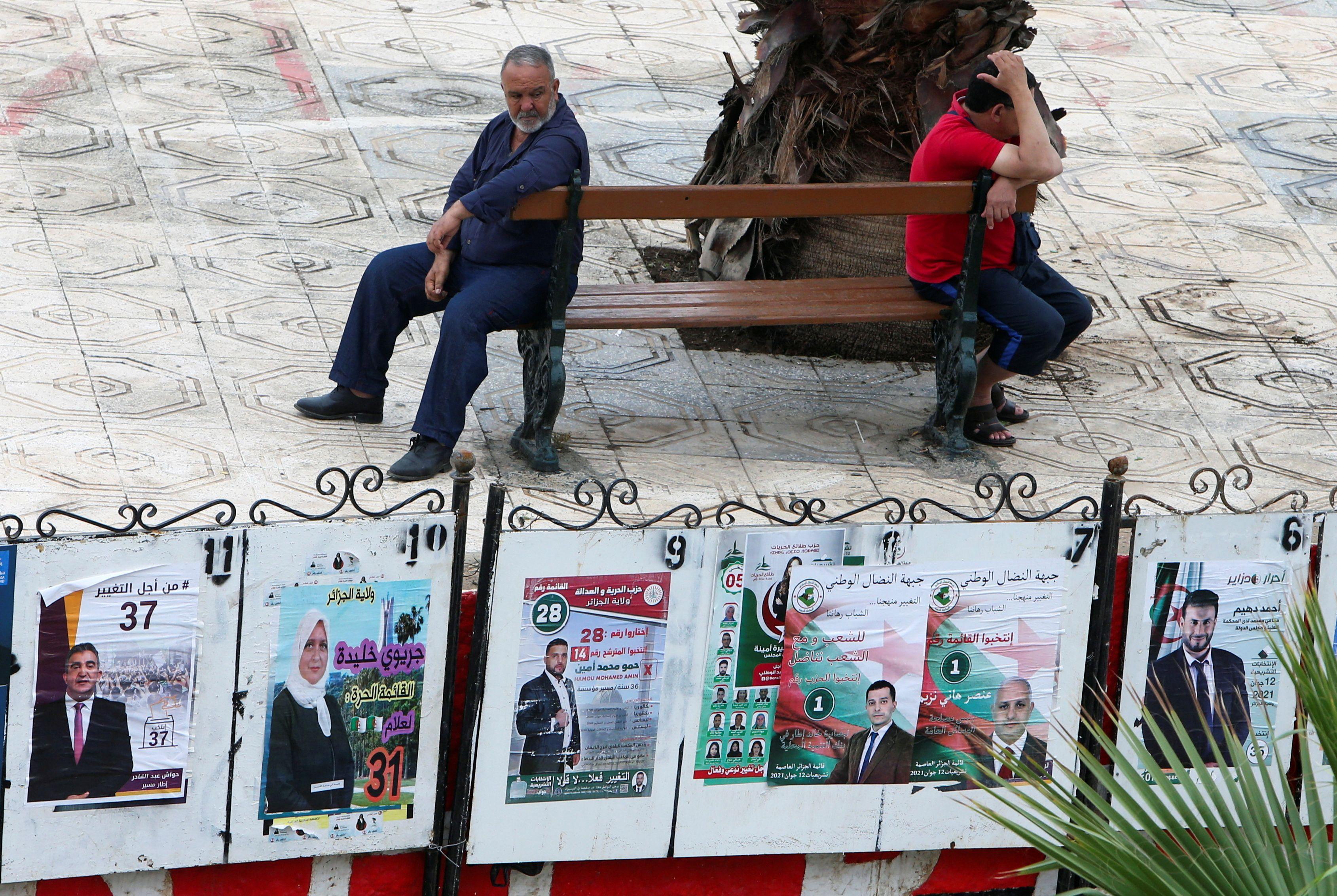 Men sit near parliamentary election campaign posters, ahead of the legislative elections, in Algiers, Algeria June 6, 2021. REUTERS/Ramzi Boudina
