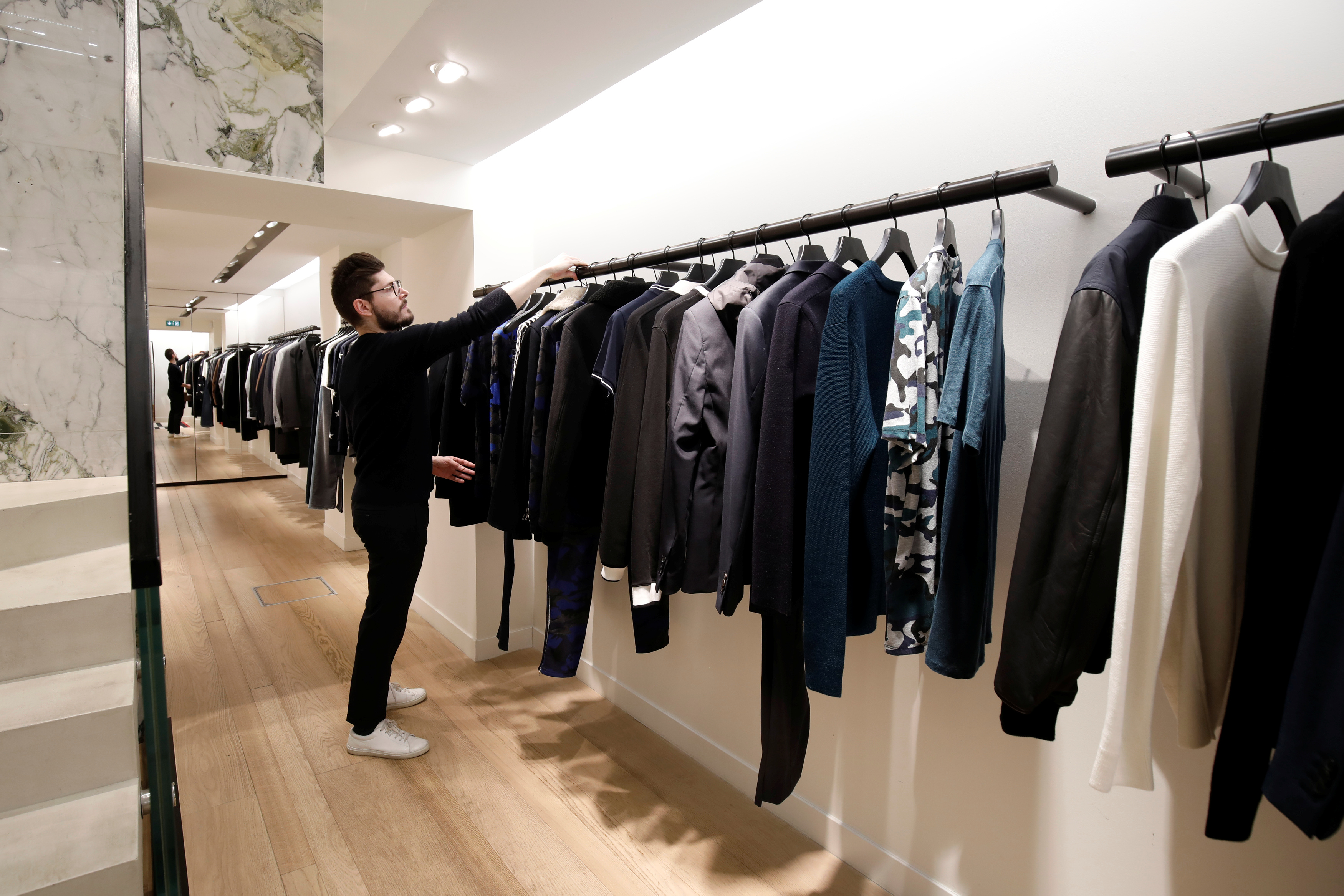 An employee arranges a clothing display inside a Sandro luxury clothing store, operated by SMCP Group, in Paris, France, December 21, 2017. REUTERS/Benoit Tessier