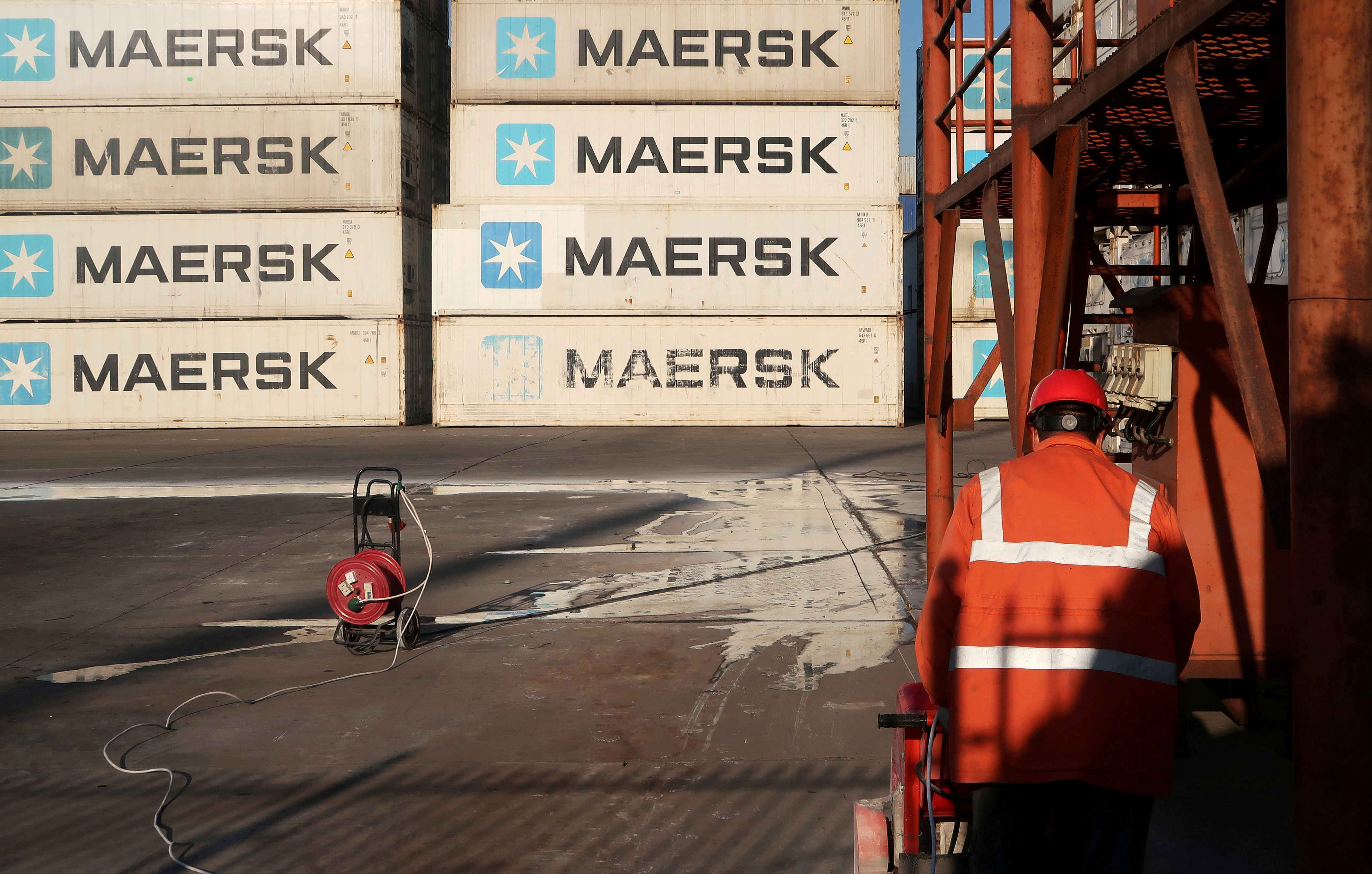 A worker is seen next to Maersk shipping containers at a logistics center nearTianjin port, in Tianjin, China December 12, 2019. REUTERS/Yilei Sun