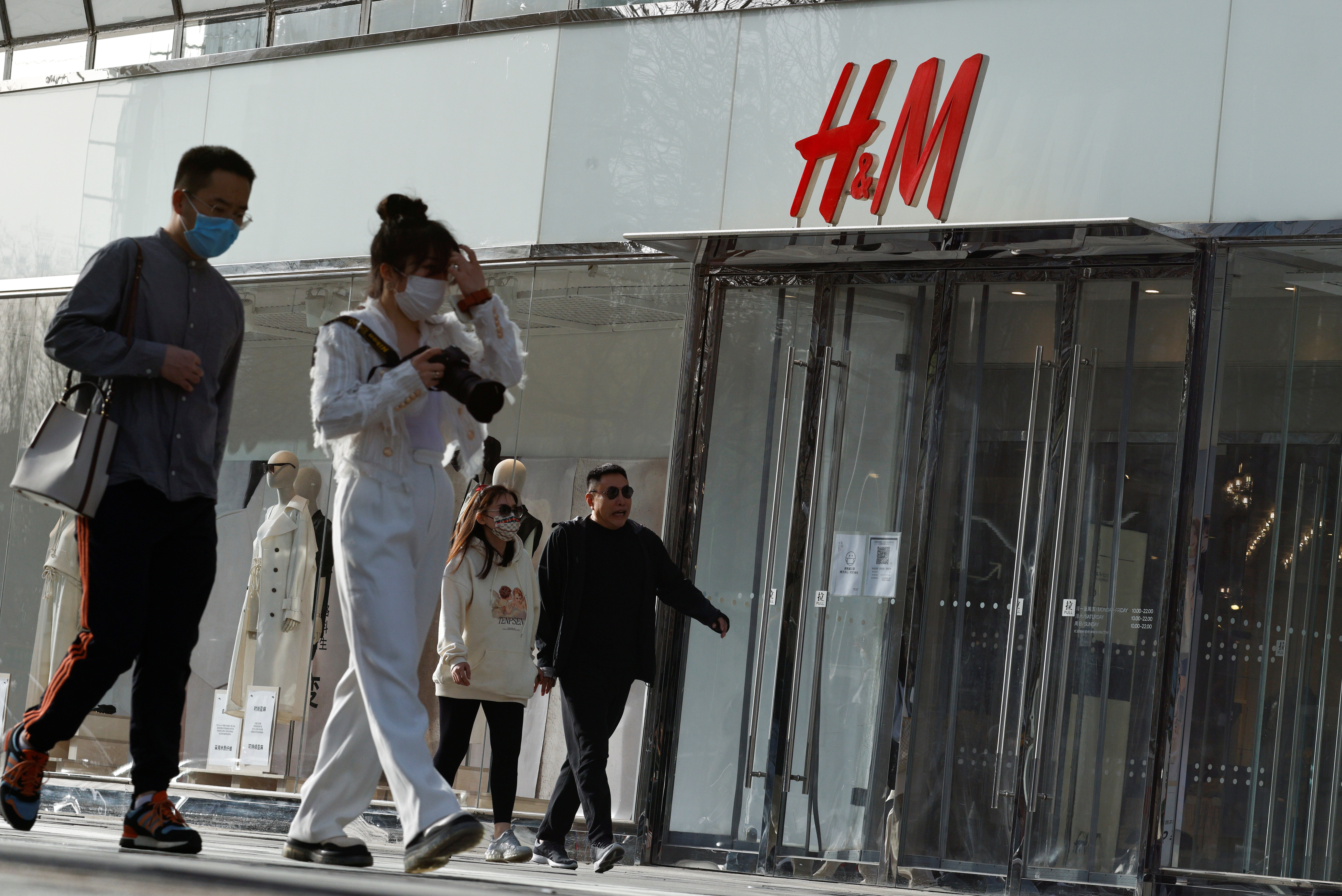 People walk past an H&M store in a shopping area in Beijing, China, March 28, 2021. REUTERS/Thomas Peter