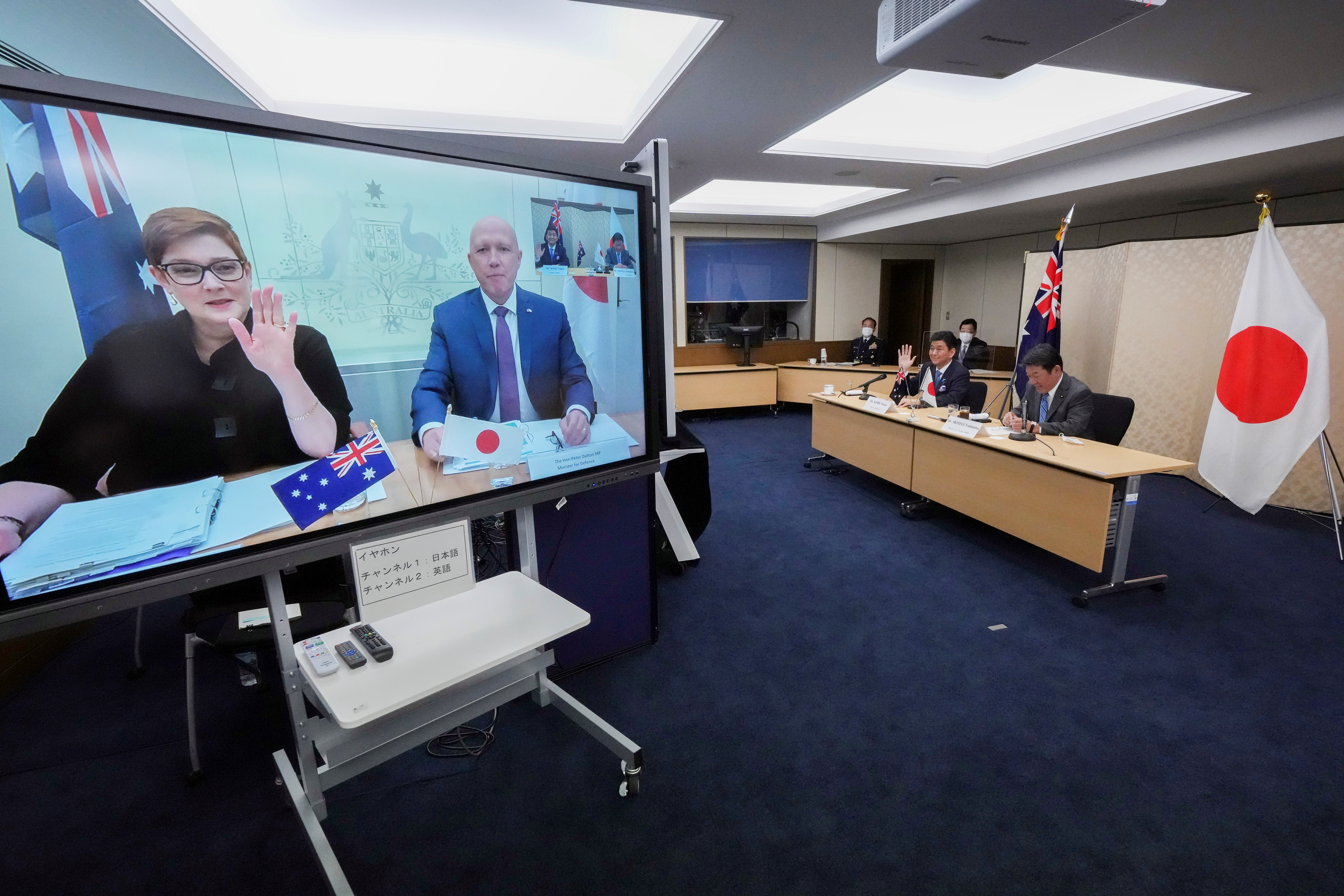 Japanese Foreign Minister Toshimitsu Motegi (R) and Defense Minister Nobuo Kishi (2nd R), attend a video conference with Australian Foreign Minister and Minister for Women Marise Payne (L) on screen, and Australian Defense Minister Peter Dutton at Foreign Ministry during their