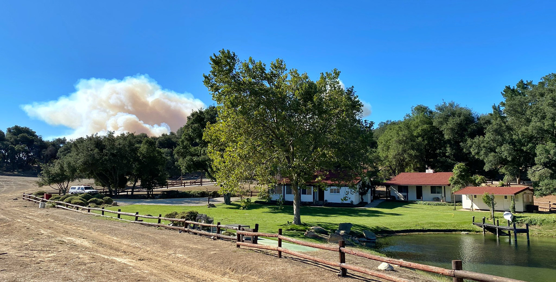 A smoke column from the Alisal Fire builds in the distance behind former U.S. President Ronald Reagan's Rancho del Cielo in Santa Barbara County near Goleta, California, U.S. October 12, 2021. The fire department said that the blaze was several miles from the ranch, with good defensible space, and several U.S. Forest Service fire engines were arriving to provide structure protection.  Mike Eliason/SBCo FD/Handout via REUTERS.