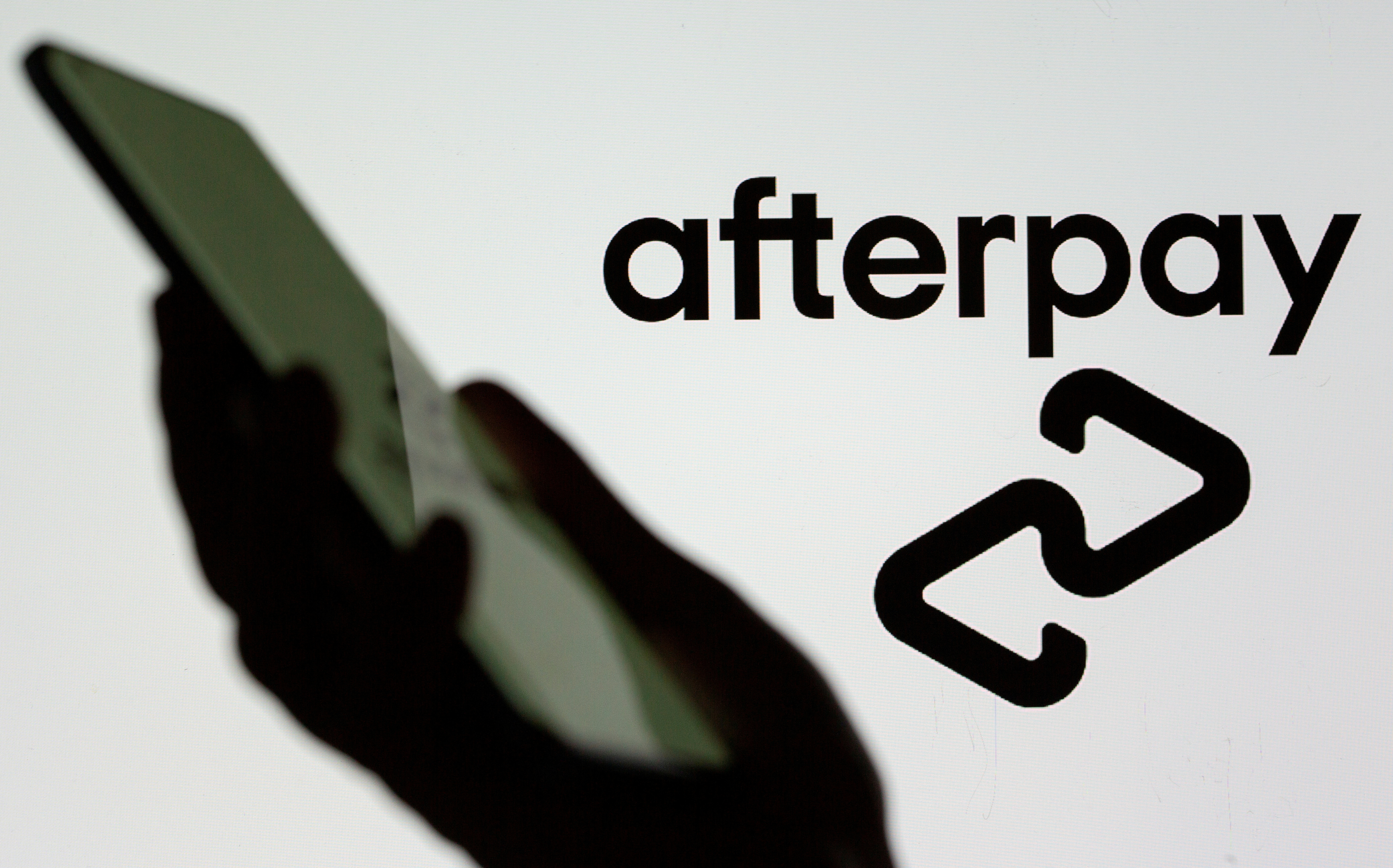 A smartphone is held in front of a displayed Afterpay logo in this illustration taken, August 2, 2021. REUTERS/Dado Ruvic/Illustration/File Photo