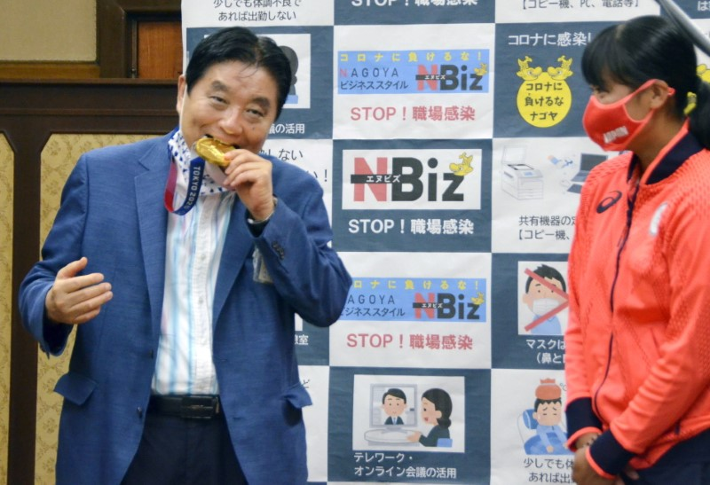 Nagoya city Mayor Takashi Kawamura bites the Tokyo 2020 Olympic Games gold medal of the softball athlete Miu Goto during a ceremony in Nagoya, central Japan, August 4, 2021, in this photo taken by Kyodo. Picture taken August 4, 2021. Mandatory credit Kyodo/via REUTERS