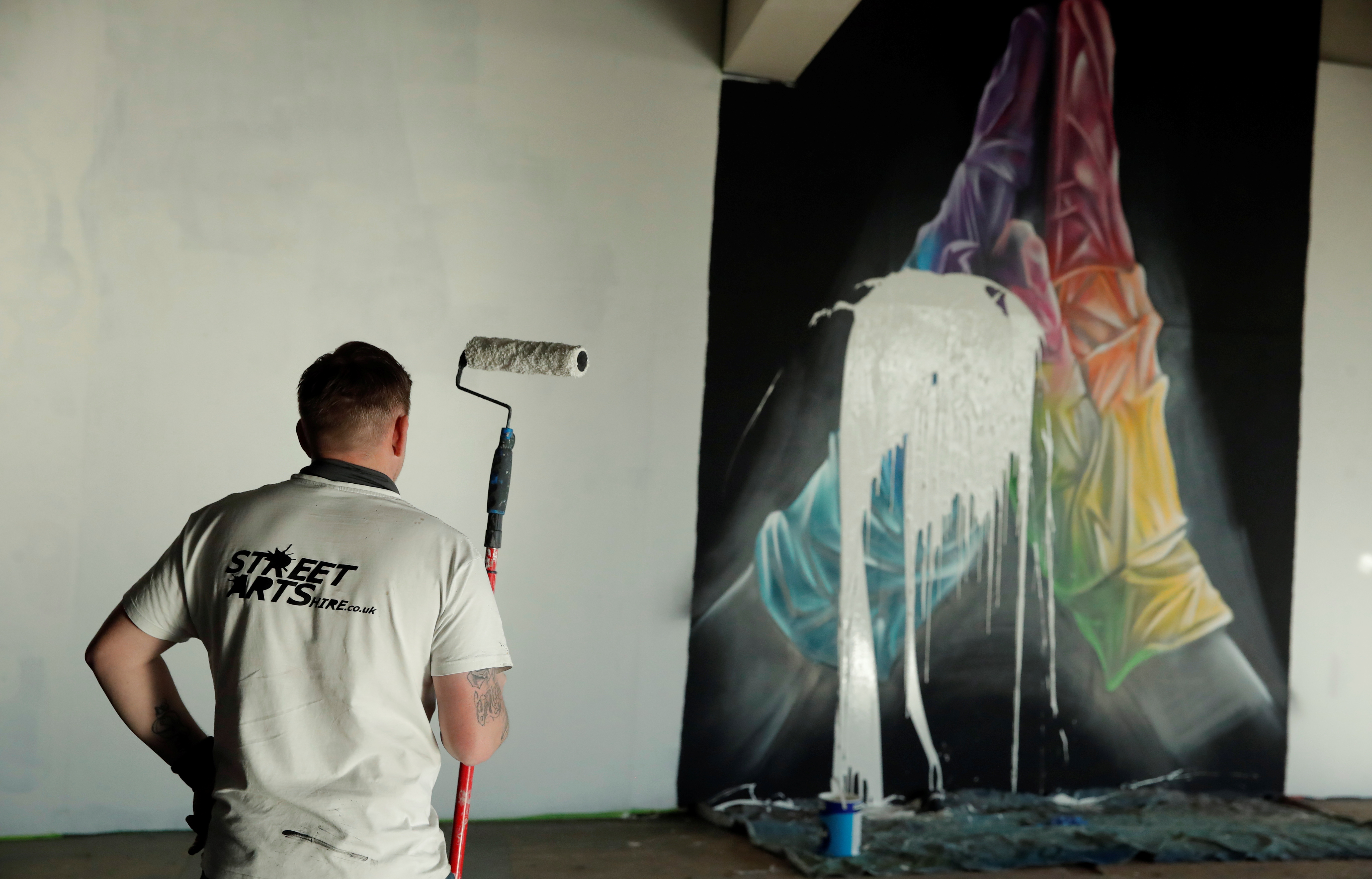 Street artist Nathan Murdoch looks at the artwork he destroyed as he creates a piece of crypto art to be auctioned with proceeds donated to the NHS in Peterborough, Britain, April 15, 2021. REUTERS/Andrew Couldridge