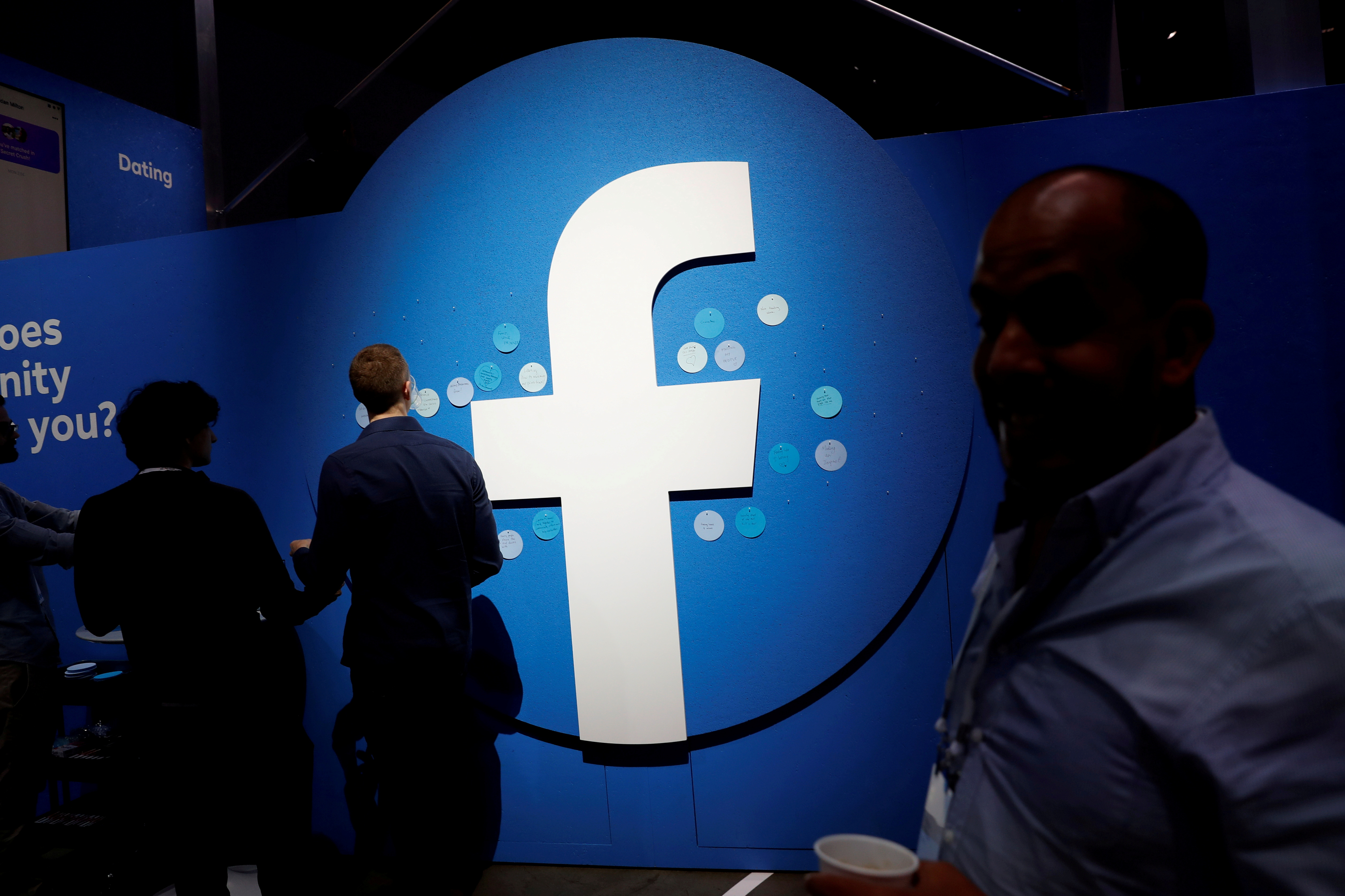 Attendees walk past a Facebook logo during Facebook Inc's F8 developers conference in San Jose, California, U.S., April 30, 2019.  REUTERS/Stephen Lam/File Photo