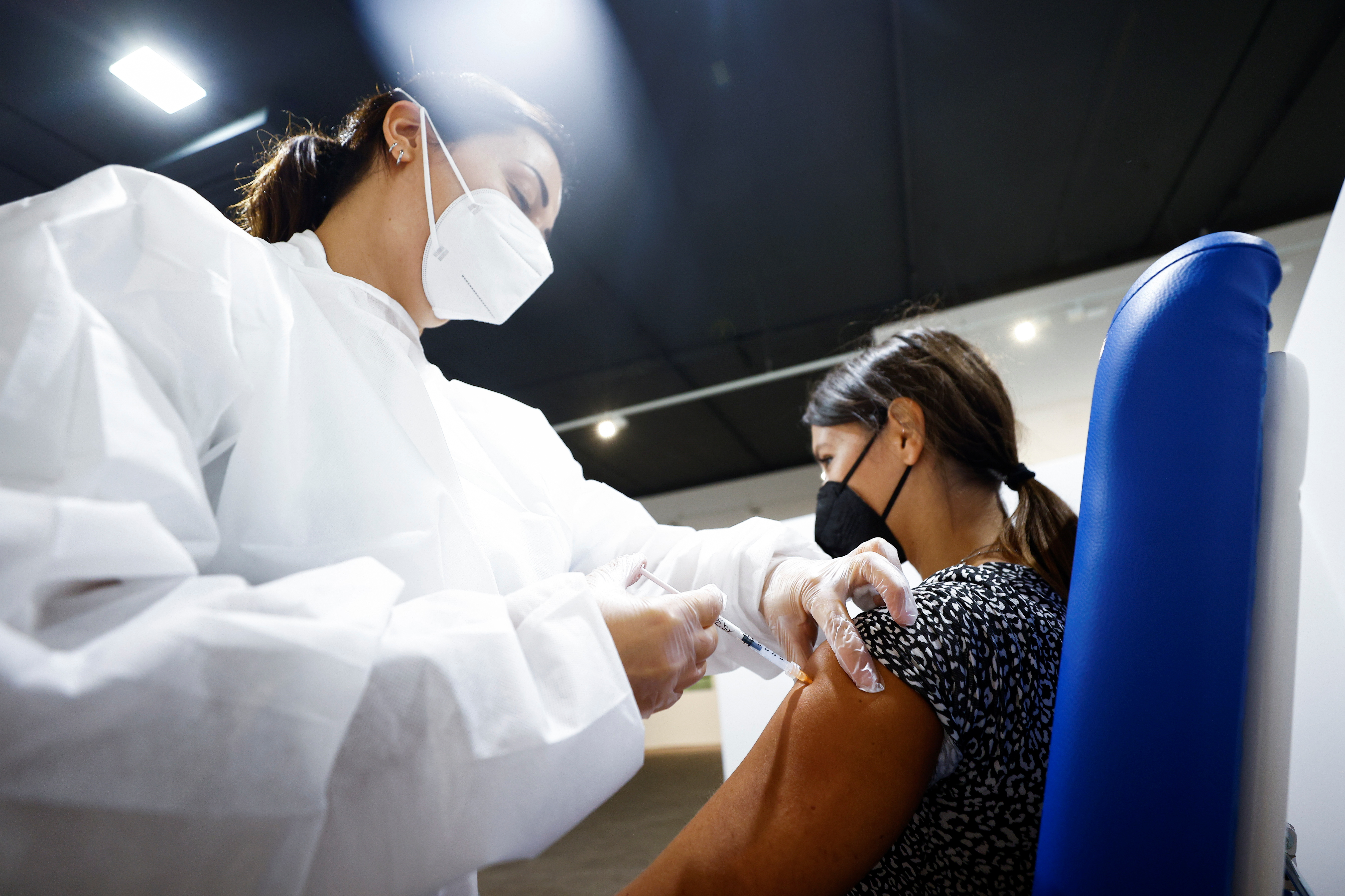 A woman receives a dose of the Moderna vaccine against the coronavirus disease (COVID-19), a day before the wider Green Pass restrictions, where Italians will need proof of immunity to access an array of services and leisure activities, come into force, at the Music Auditorium in Rome, Italy, August 5, 2021. REUTERS/Guglielmo Mangiapane
