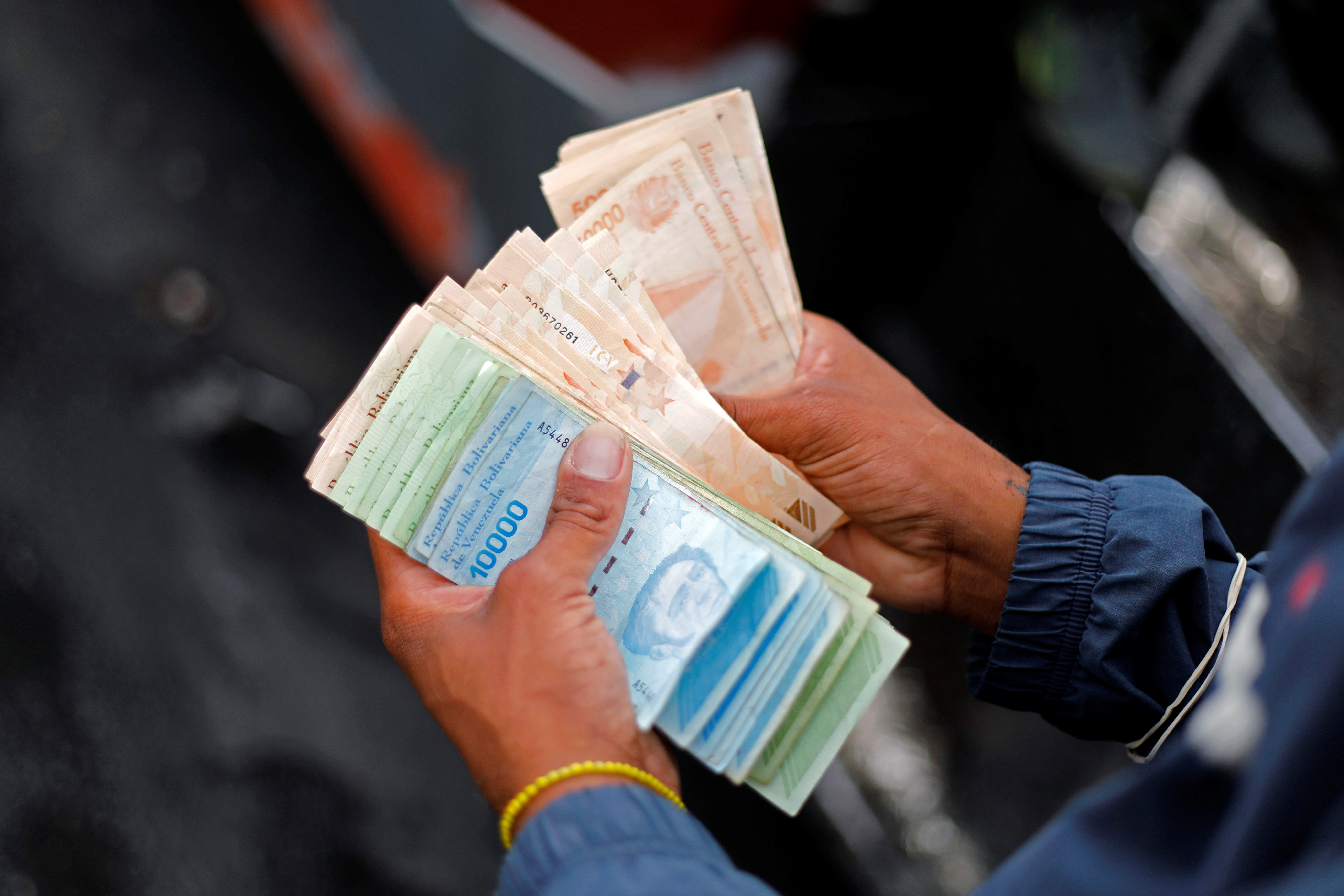A bus driver's assistant counts a wad of Bolivar banknotes at a bus stop outside the Antimano metro station in Caracas, Venezuela, March 9, 2021. Picture taken March 9, 2021. REUTERS/Leonardo Fernandez Viloria