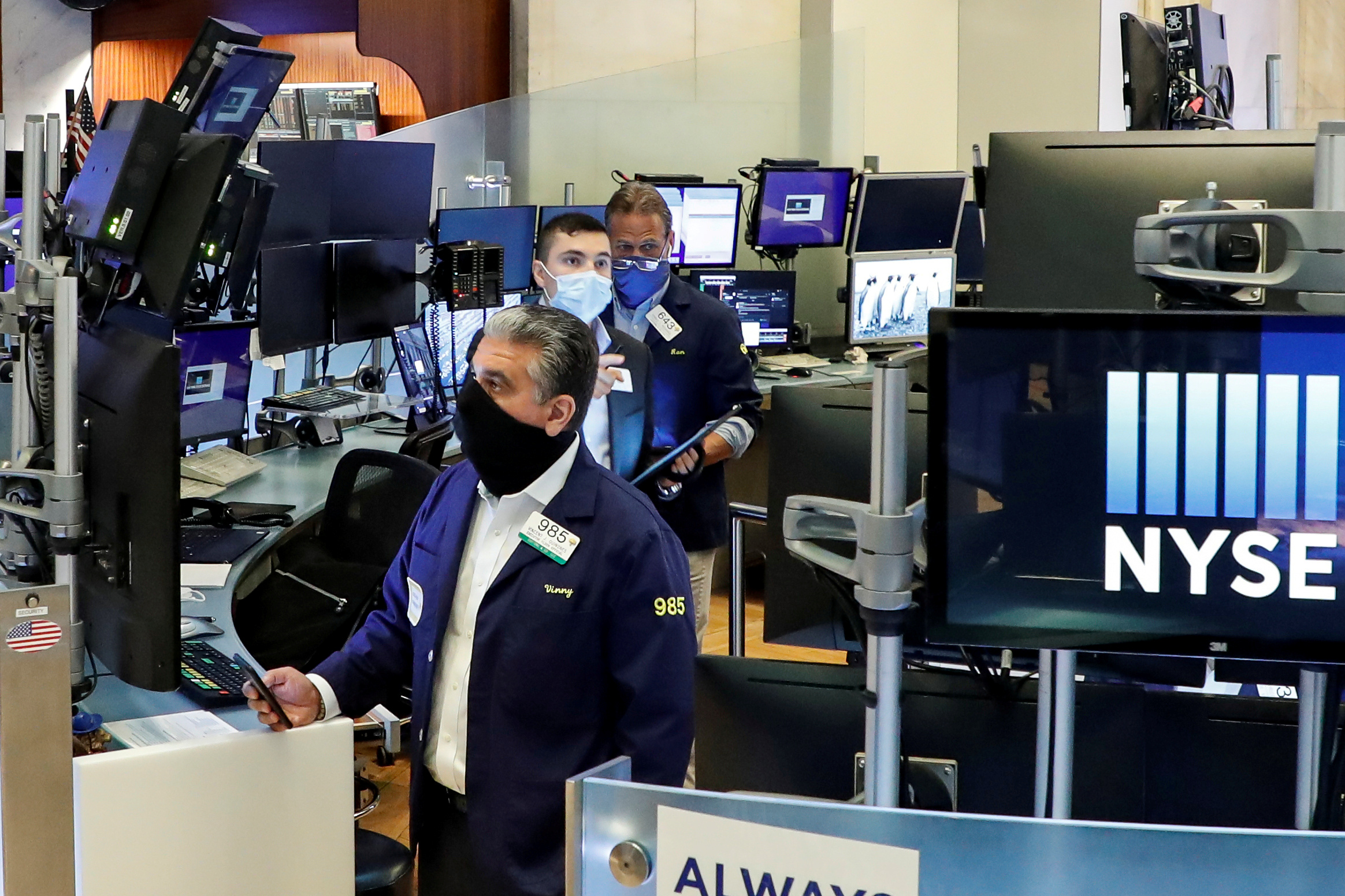 Traders wearing masks work, on the first day of in-person trading since the closure during the outbreak of the coronavirus disease (COVID-19) on the floor at the New York Stock Exchange (NYSE) in New York, U.S., May 26, 2020. REUTERS/Brendan McDermid