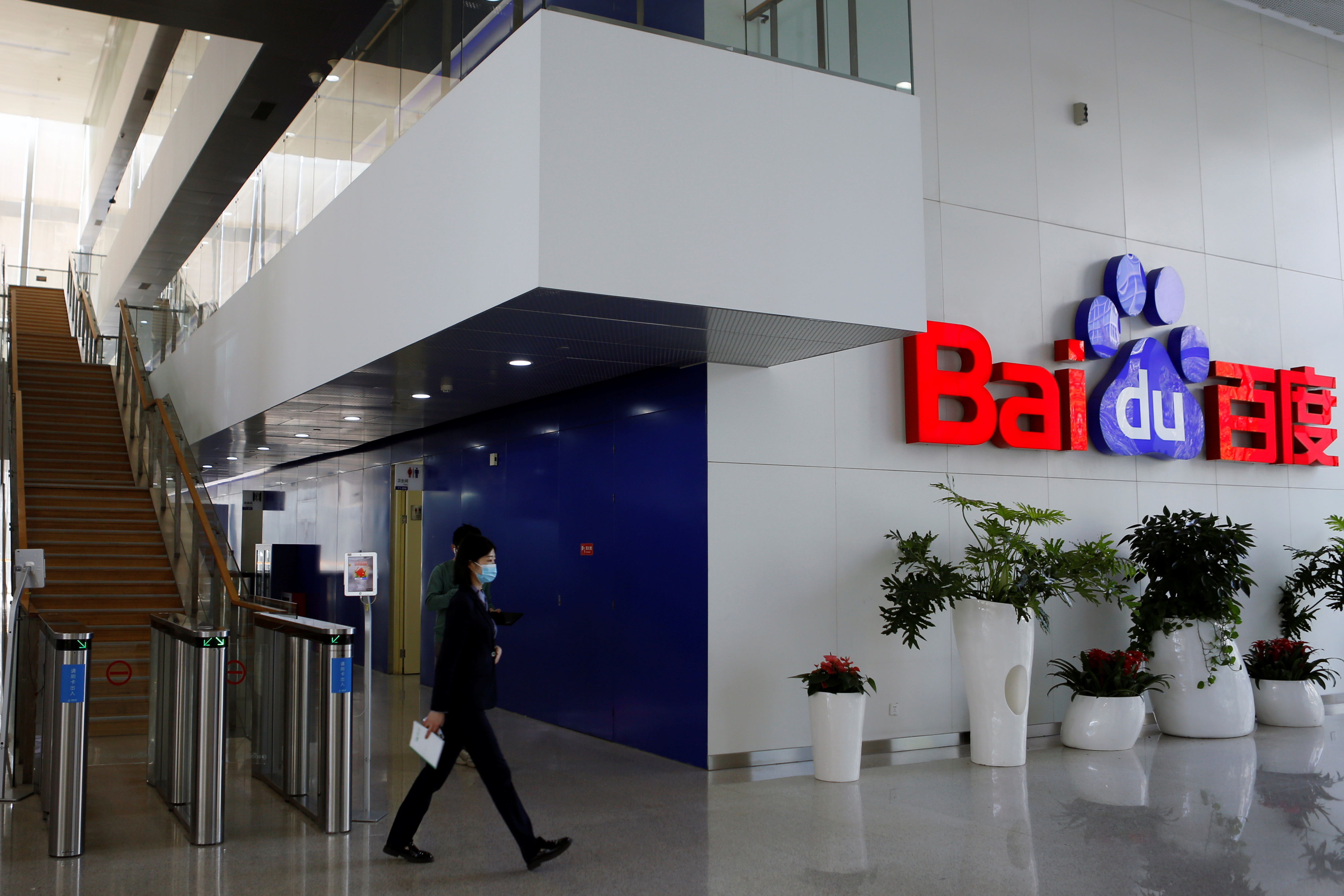 People walk near a Baidu logo at the company headquarters in Beijing, China April 23, 2021. REUTERS/Florence Lo