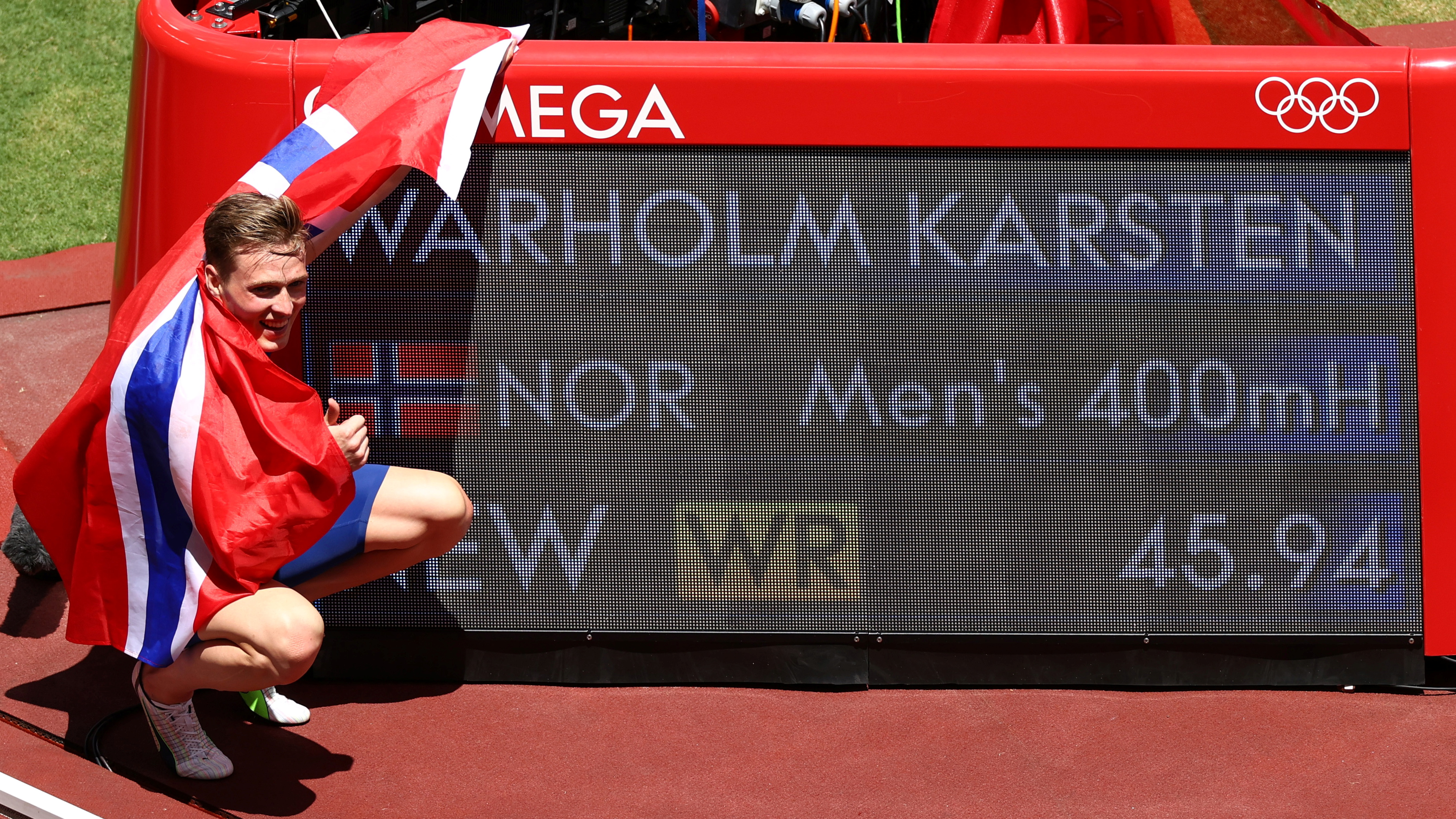 Tokyo 2020 Olympics - Athletics - Men's 400m Hurdles - Final - Olympic Stadium, Tokyo, Japan - August 3, 2021. Karsten Warholm of Norway poses next to his new world record as he celebrates after winning gold. REUTERS/Andrew Boyers