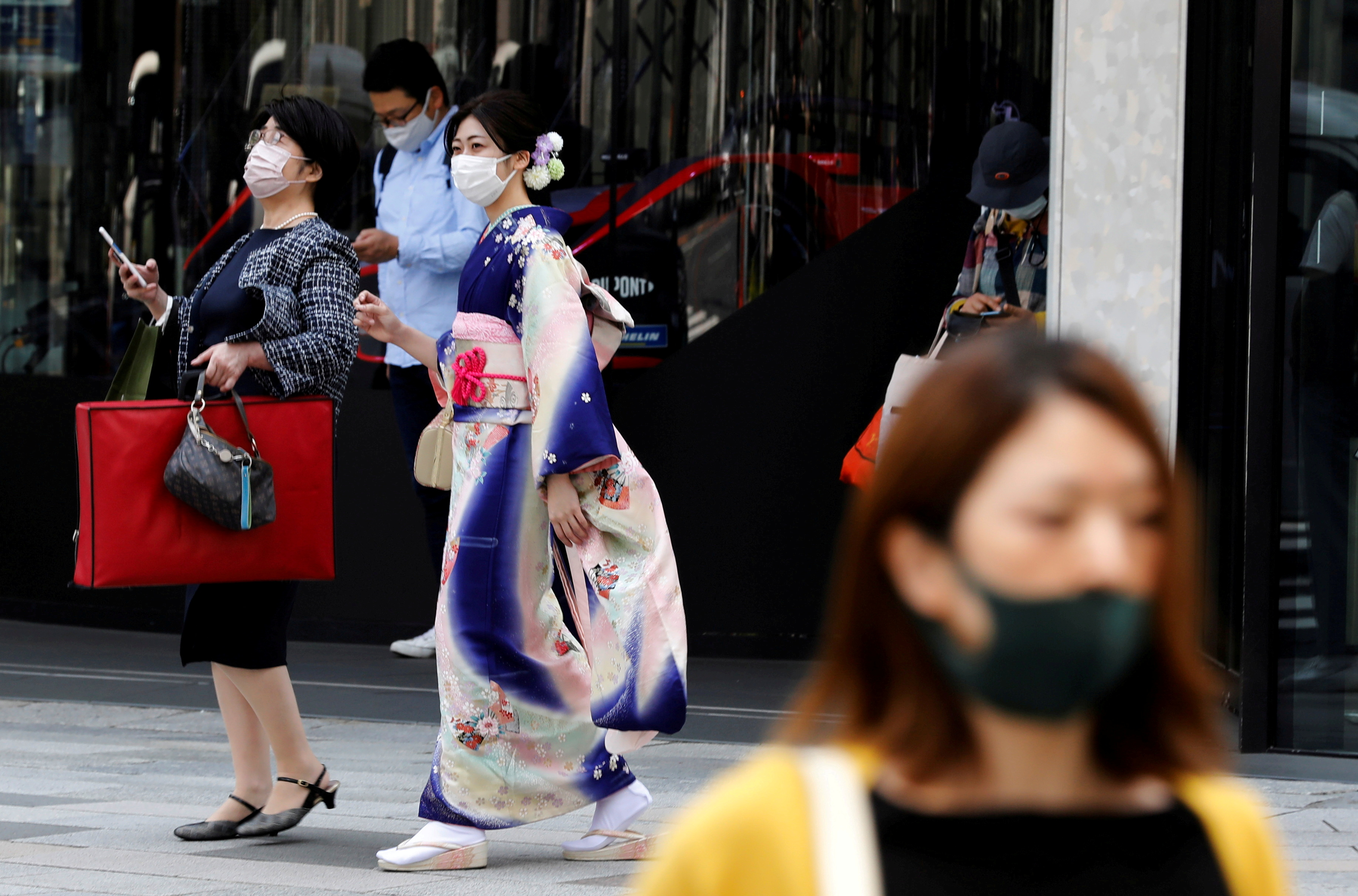 A woman in kimono clad and pedestrians wearing protective face masks, make their way at a shopping district on the first day of the country's third state of emergency, amid  the coronavirus disease (COVID-19) outbreak, in Tokyo, Japan, April 25, 2021.   REUTERS/Kim Kyung-Hoon/File Photo