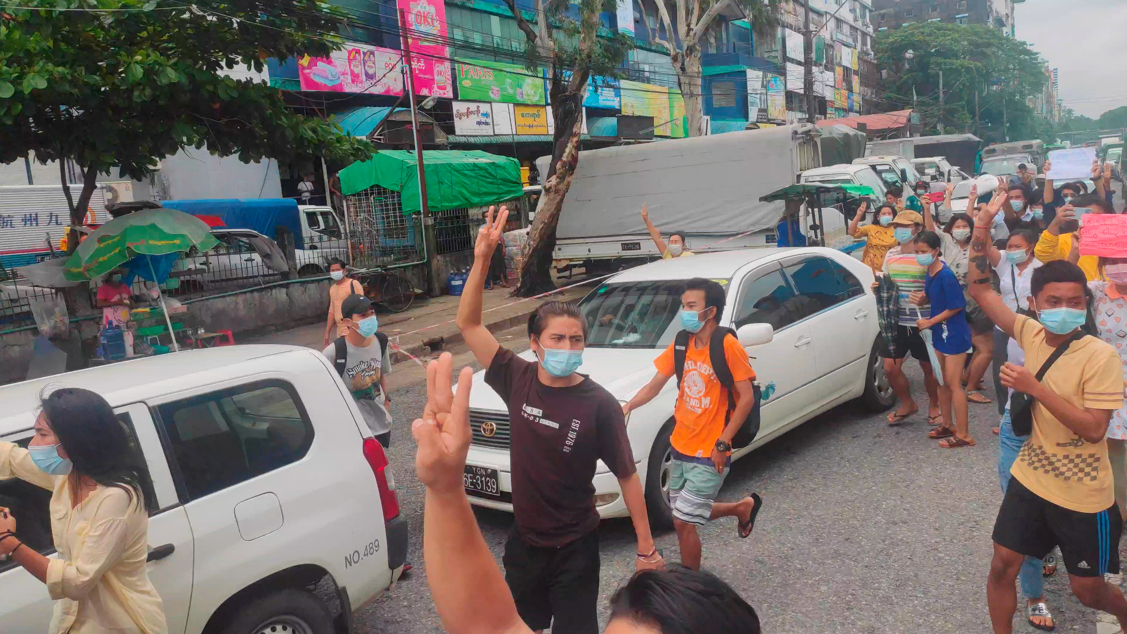 Demonstrators show a three-finger salute during a flash protest in solidarity with the Mandalay People?s Defence Force, in Yangon, Myanmar June 22, 2021. in this screengrab obtained by Reuters from a social media video.