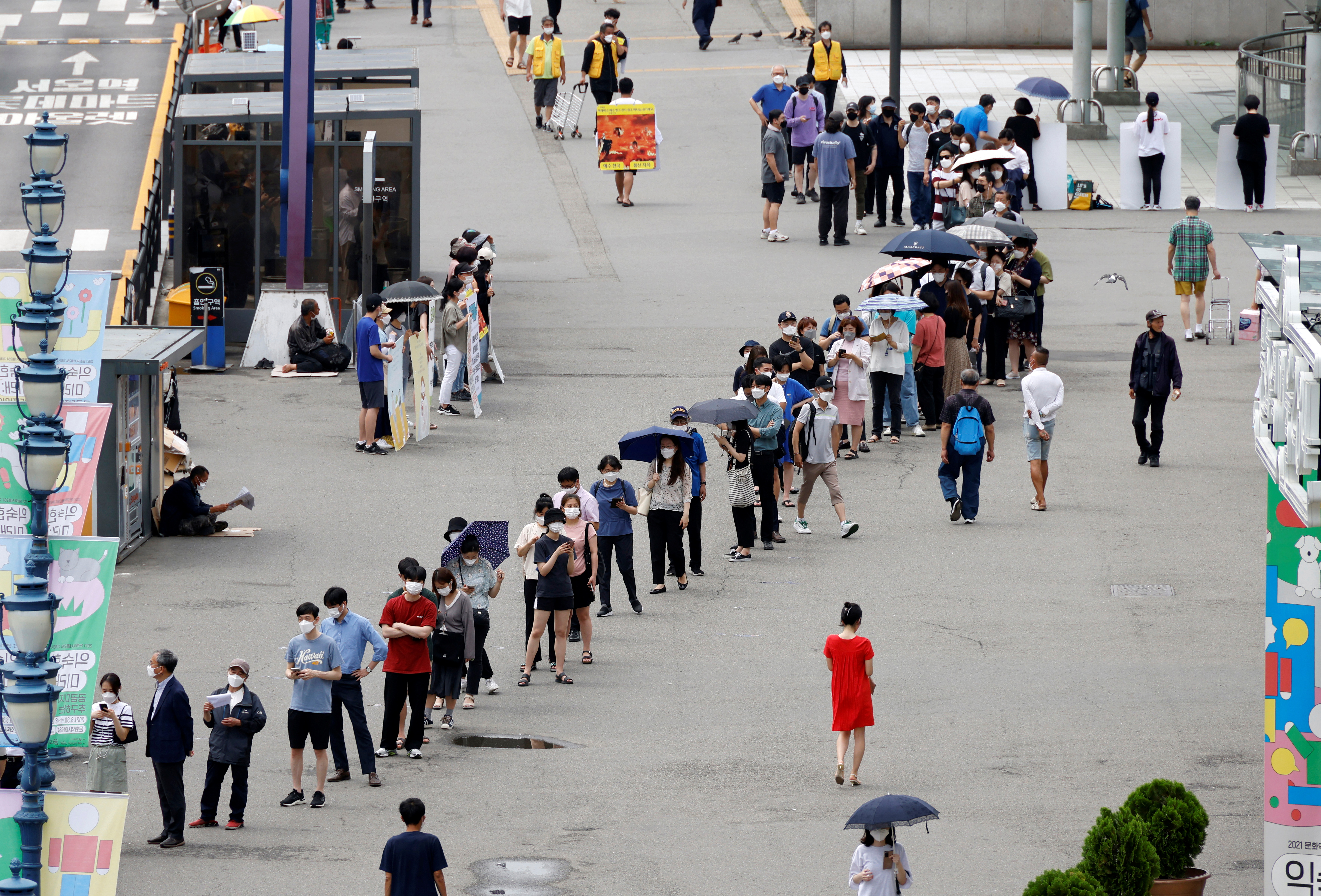 People wait in line for a coronavirus disease (COVID-19) test at a testing site which is temporarily set up at a railway station in Seoul, South Korea, July 7, 2021.  REUTERS/ Heo Ran