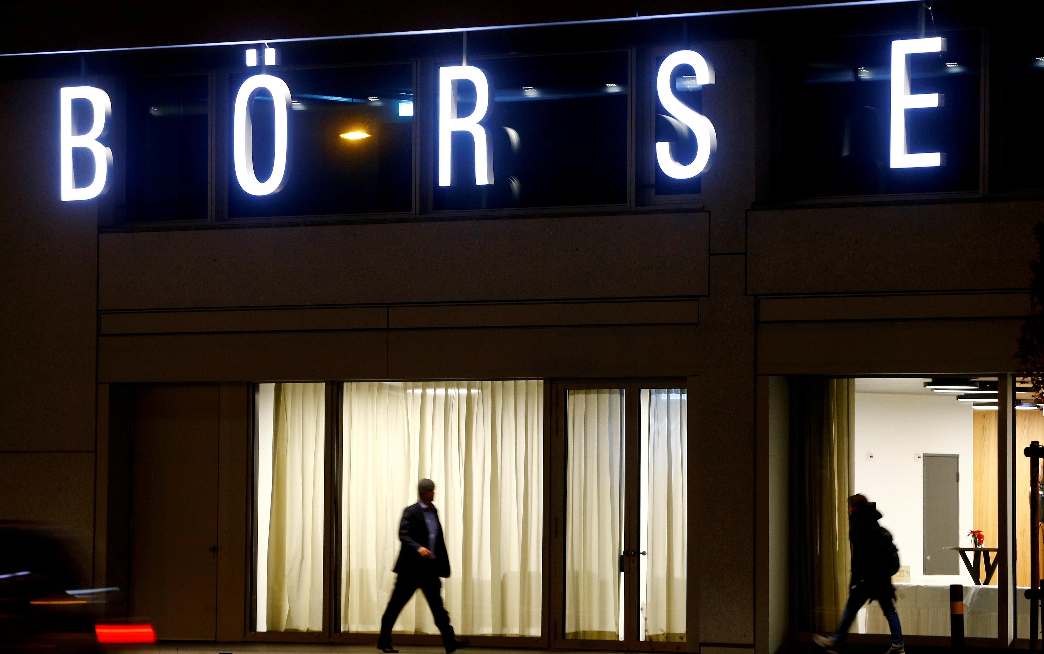 A man walks under the illuminated word