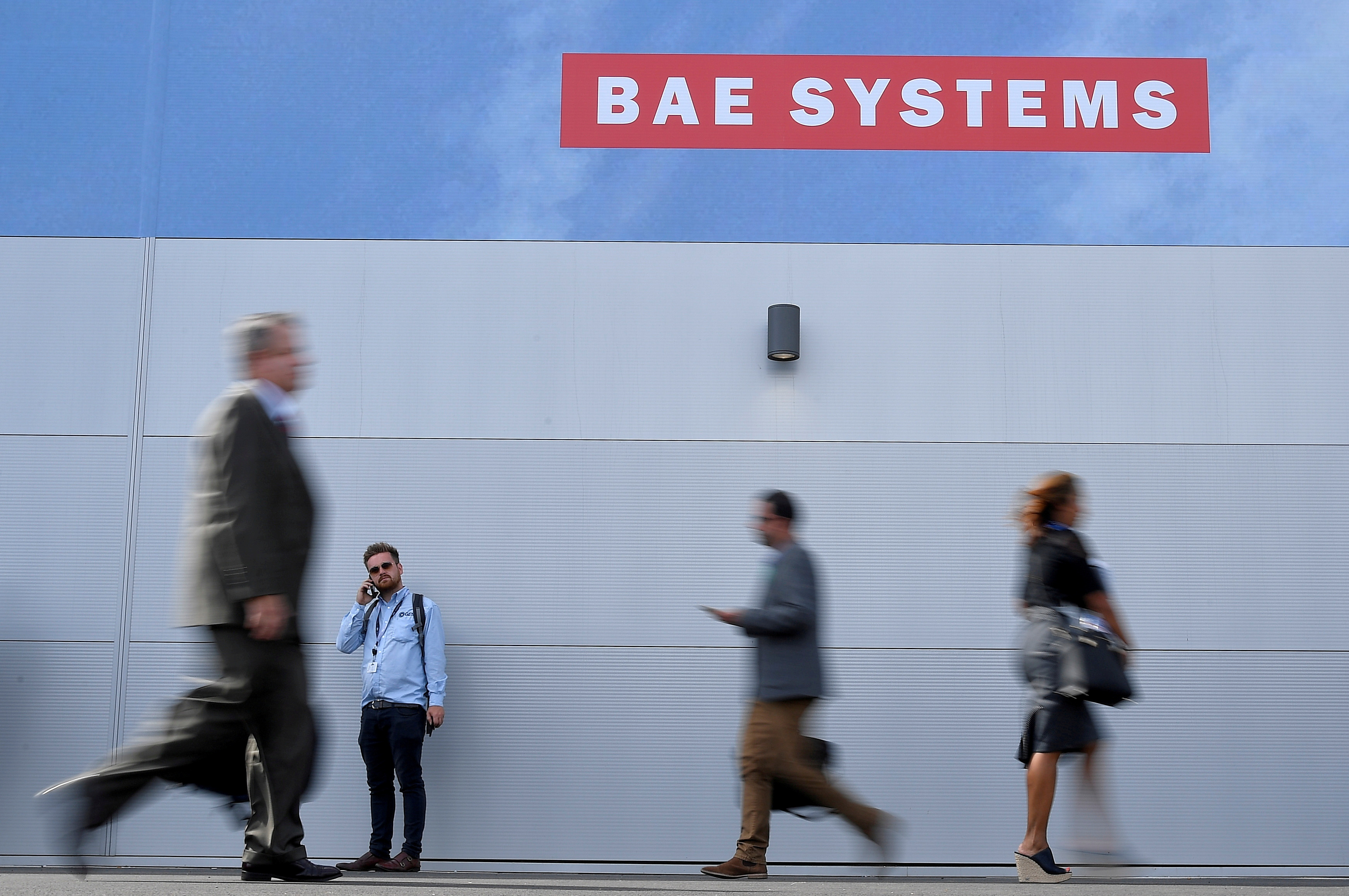 Trade visitors walk past an advertisement for BAE Systems at Farnborough International Airshow in Farnborough, Britain, July 17, 2018. REUTERS/Toby Melville/File Photo