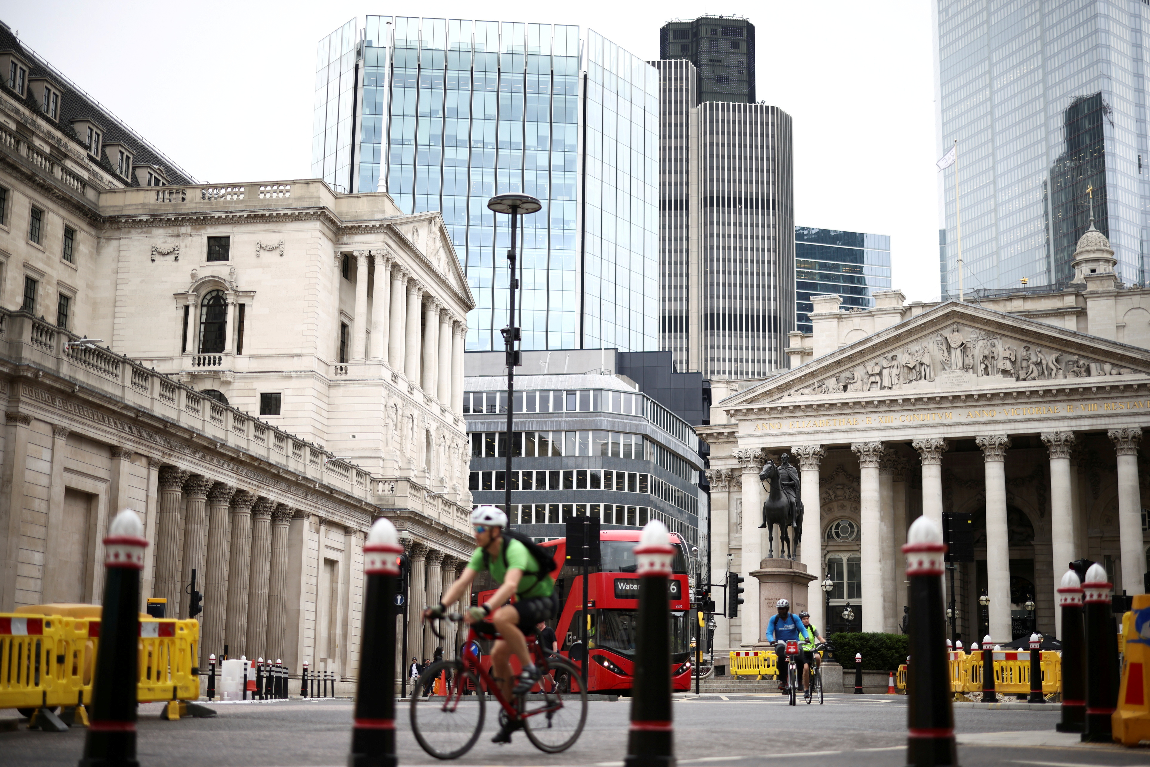 The Bank of England can be seen as people cycle through the City of London financial district, in London, Britain, June 11, 2021. REUTERS/Henry Nicholls/File Photo
