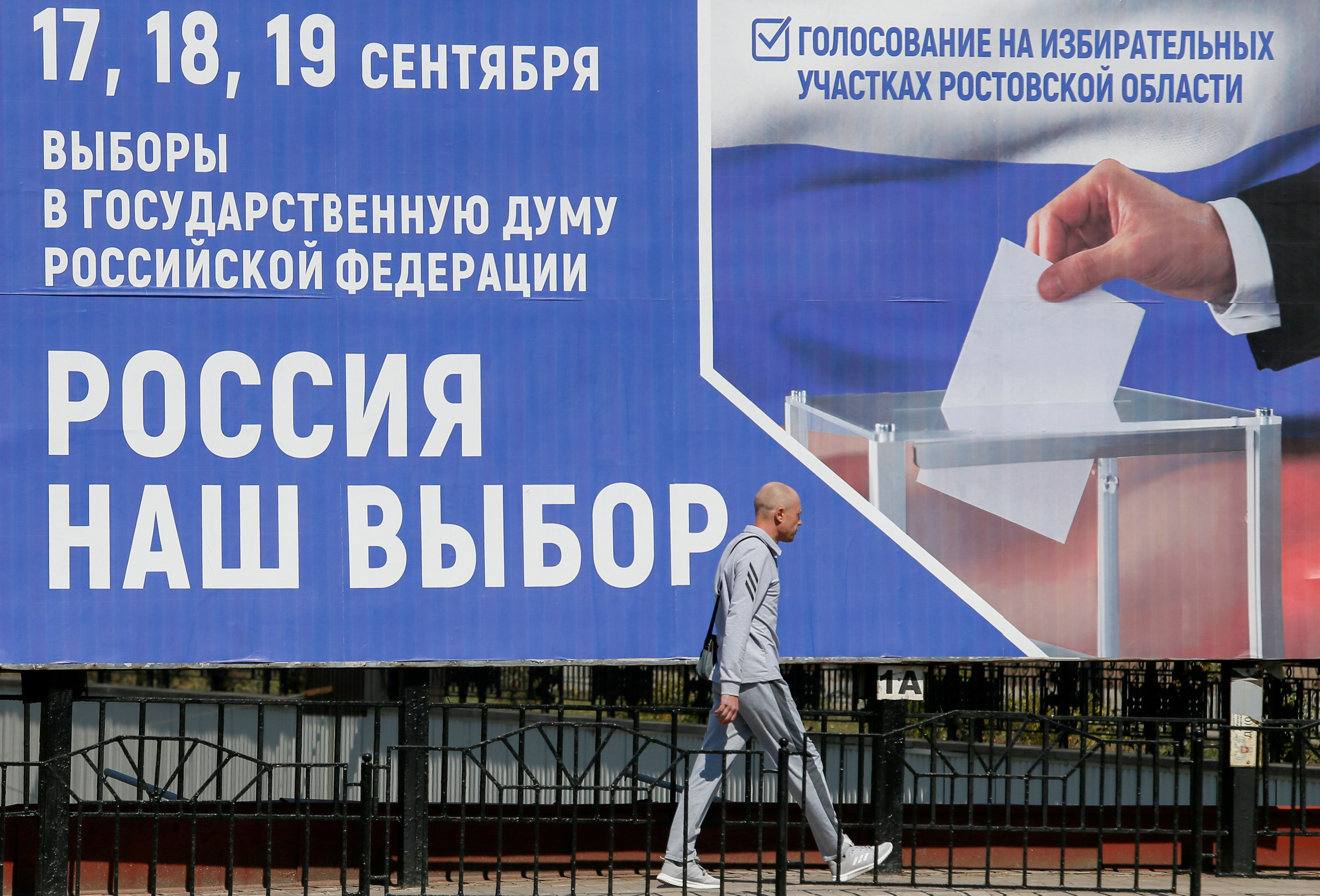 A pedestrian walks past a board informing of the upcoming Russian parliamentary elections in a street in the rebel-held city of Donetsk, Ukraine September 9, 2021. A board promotes to take part in the election by voting at polling stations in Russia's Rostov Region and reads: