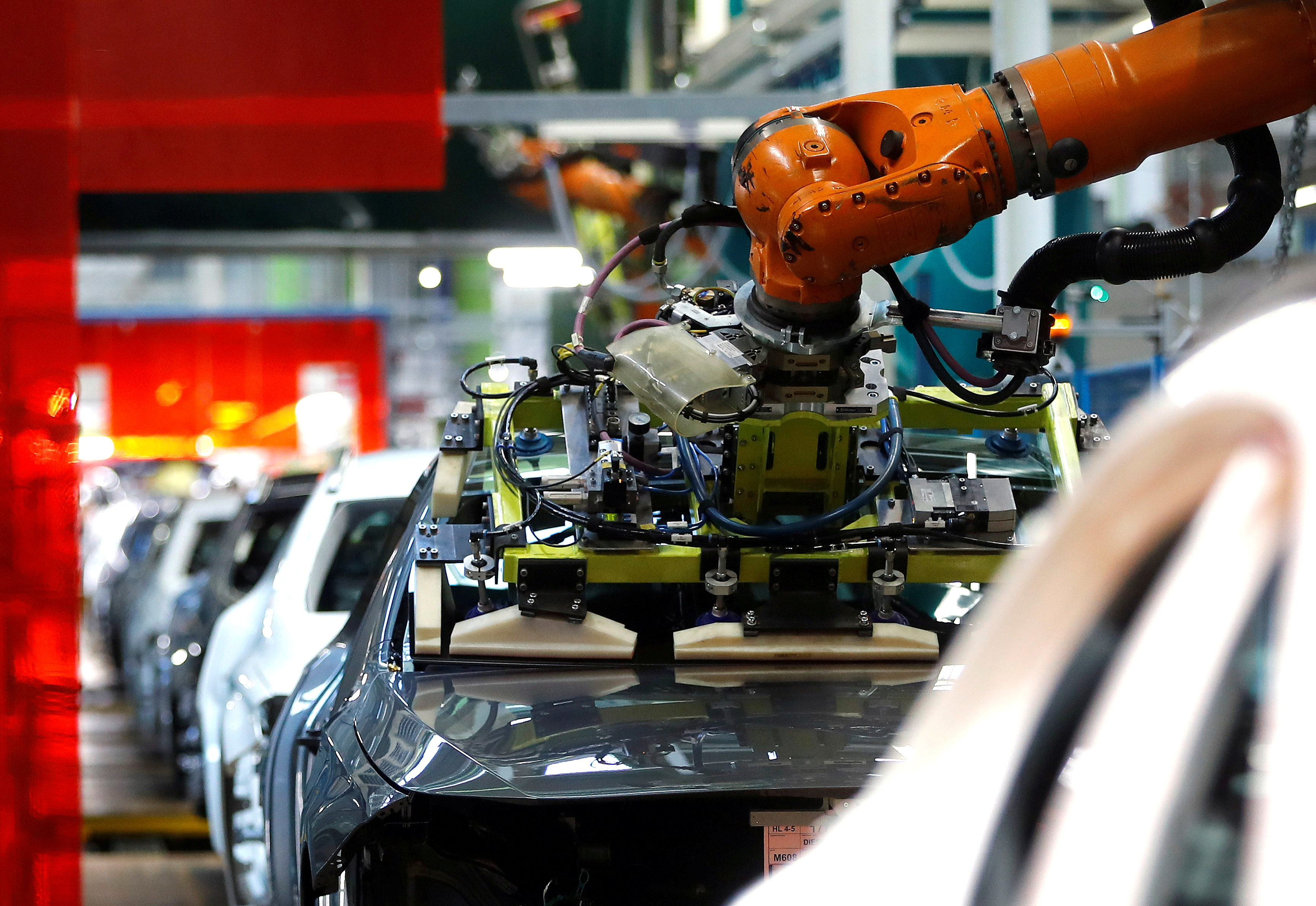 A robot engineered by Kuka adjusts a windscreen in a fully automated process on a model of the A-class production line of German car manufacturer Mercedes Benz at the Daimler factory in Rastatt, Germany, February 4, 2019. REUTERS/Kai Pfaffenbach