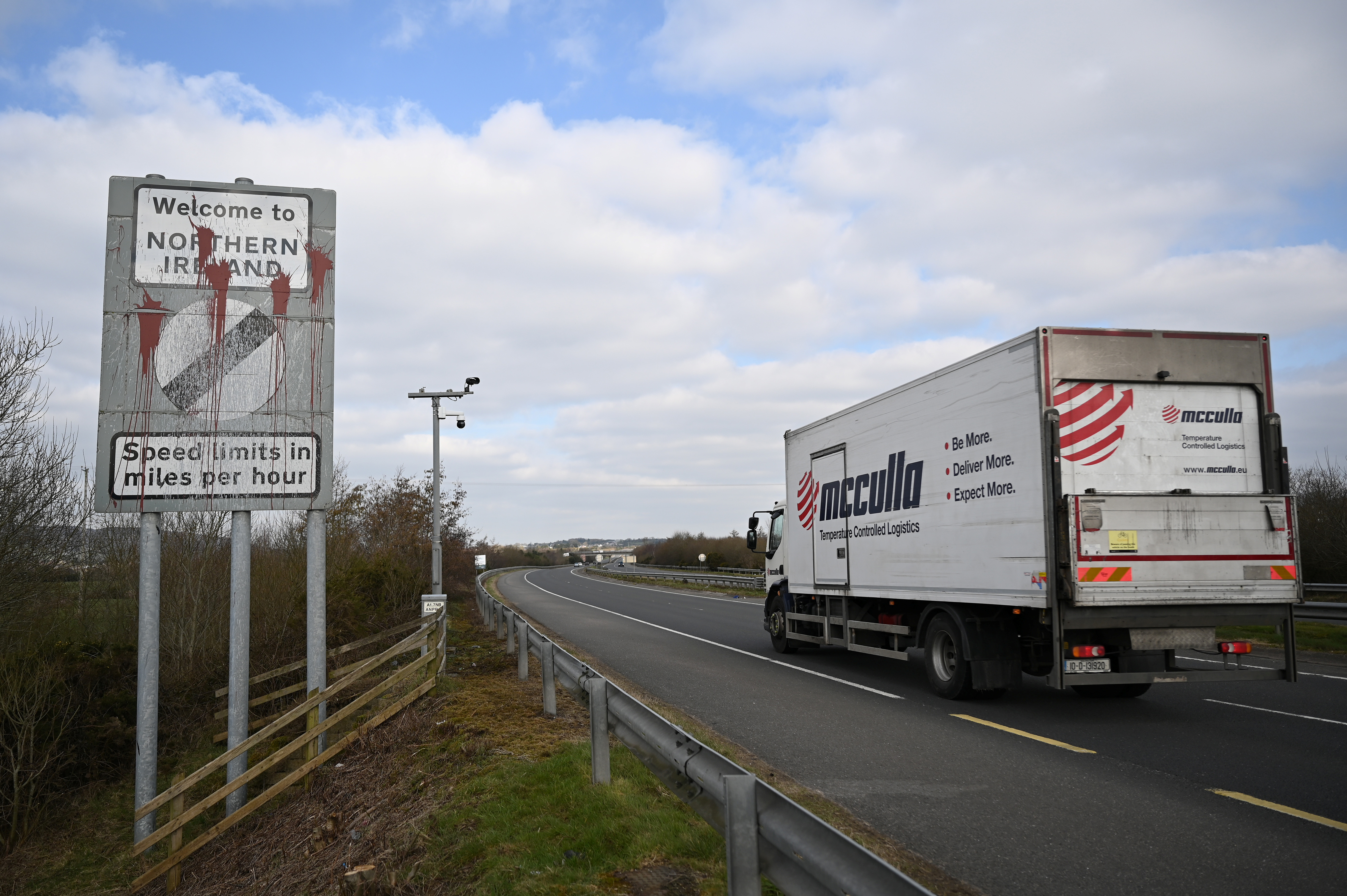 A truck drives past a defaced 'Welcome to Northern Ireland' sign on the Ireland and Northern Ireland border reminding motorists that the speed limits will change from kilometres per hour to miles per hour on the border in Carrickcarnan, Ireland, March 6, 2021. Picture taken March 6, 2021. REUTERS/Clodagh Kilcoyne