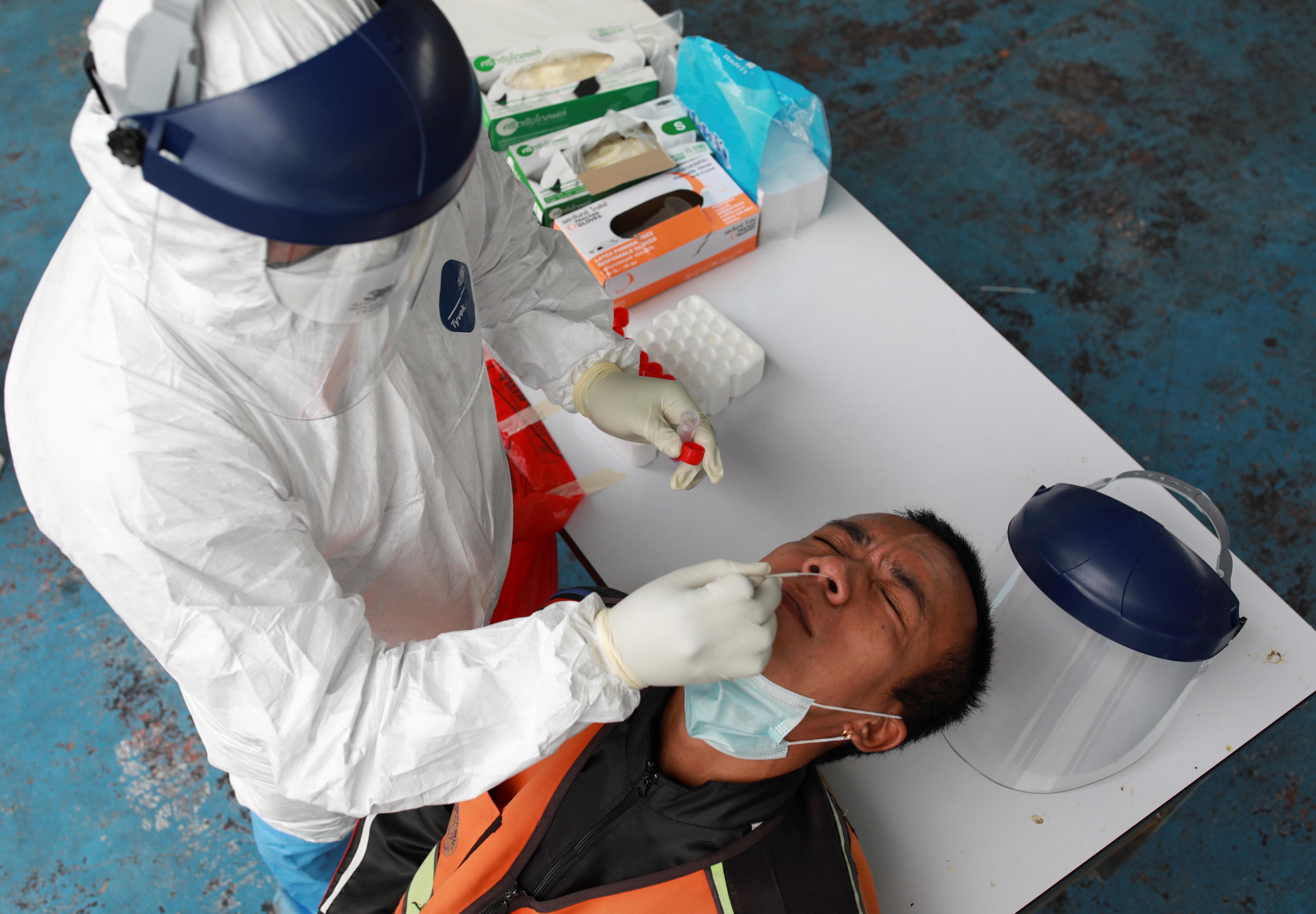A health worker takes a nasal swab sample from a man from Klong Toey community, for a coronavirus disease (COVID-19) test, in Bangkok, Thailand, May 4, 2021. REUTERS/Soe Zeya Tun