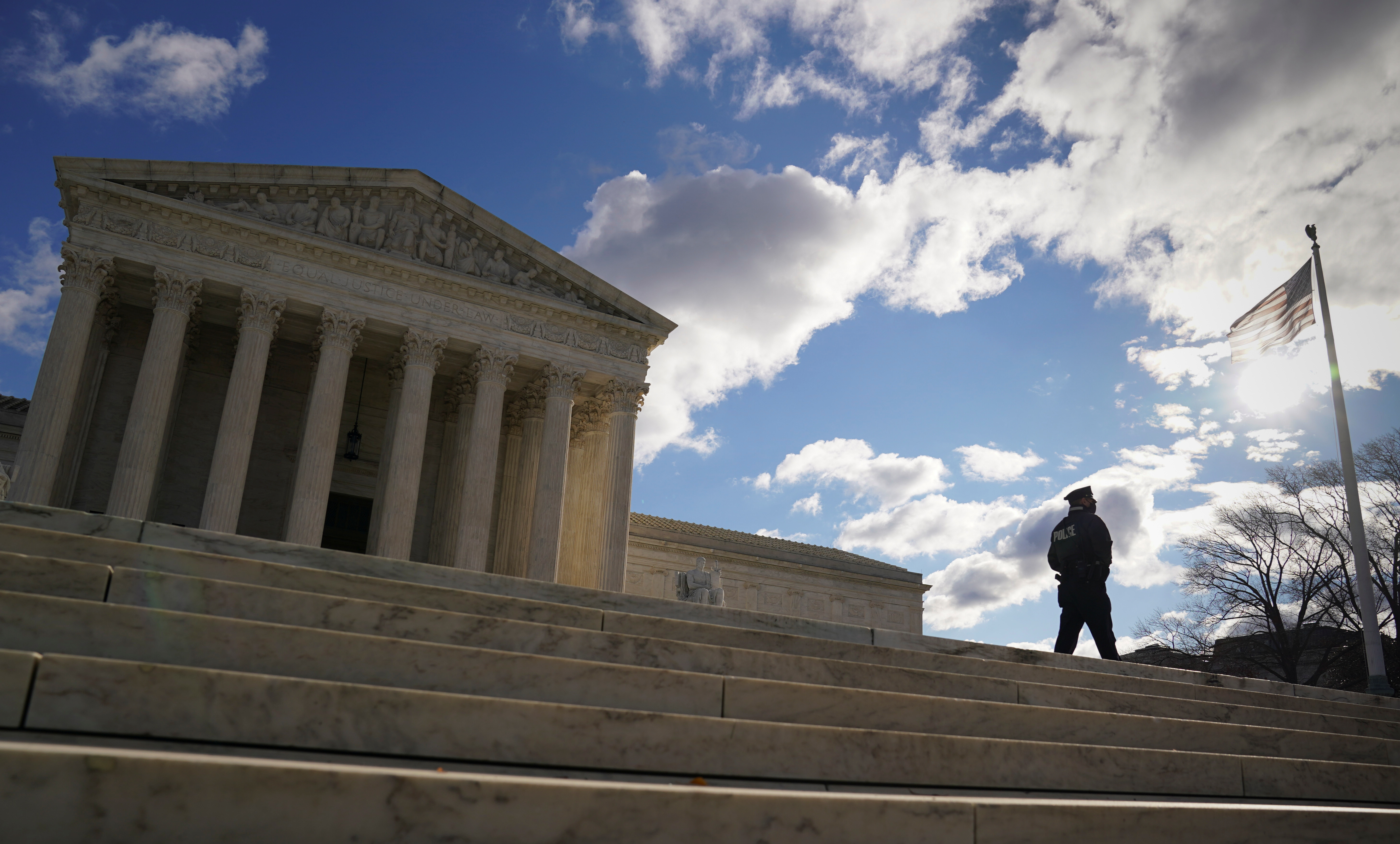 A police officer patrols the front of the U.S. Supreme Court in Washington, U.S., December 22, 2020. REUTERS/Kevin Lamarque