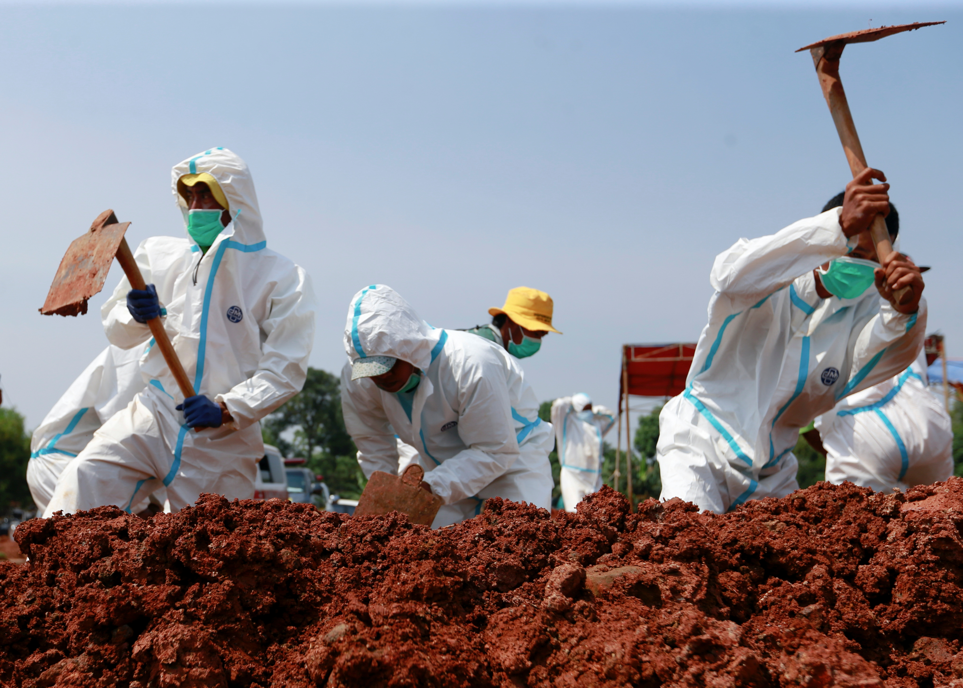 Gravediggers wearing personal protective equipment (PPE) bury a coffin at a Muslim burial area provided by the government for coronavirus disease (COVID-19) victims in Bekasi, on the outskirts of Jakarta, Indonesia, July 8, 2021. REUTERS/Ajeng Dinar Ulfiana