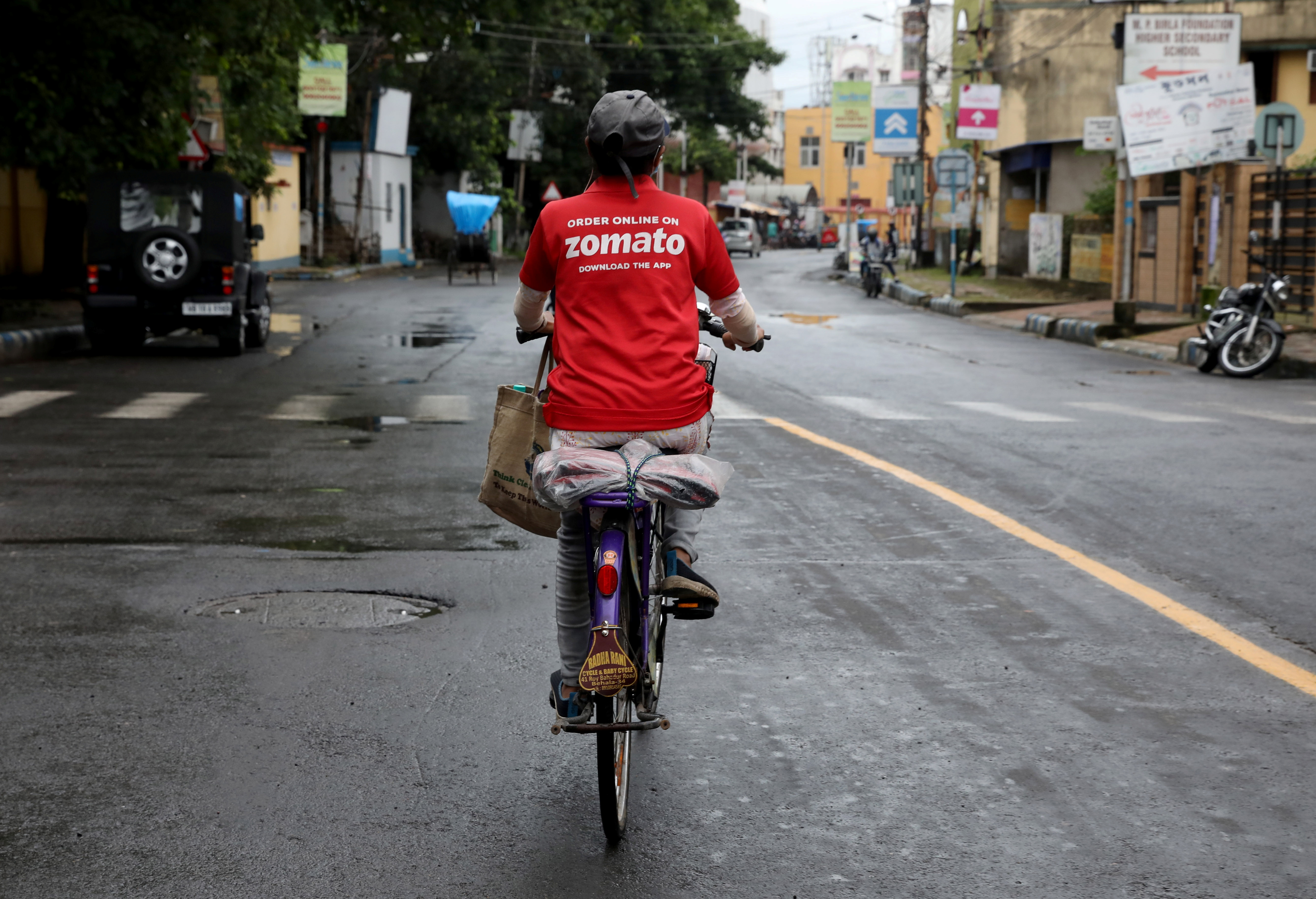 A delivery worker of Zomato, an Indian food-delivery startup, rides her bicycle along a road in Kolkata, India, July 13, 2021.