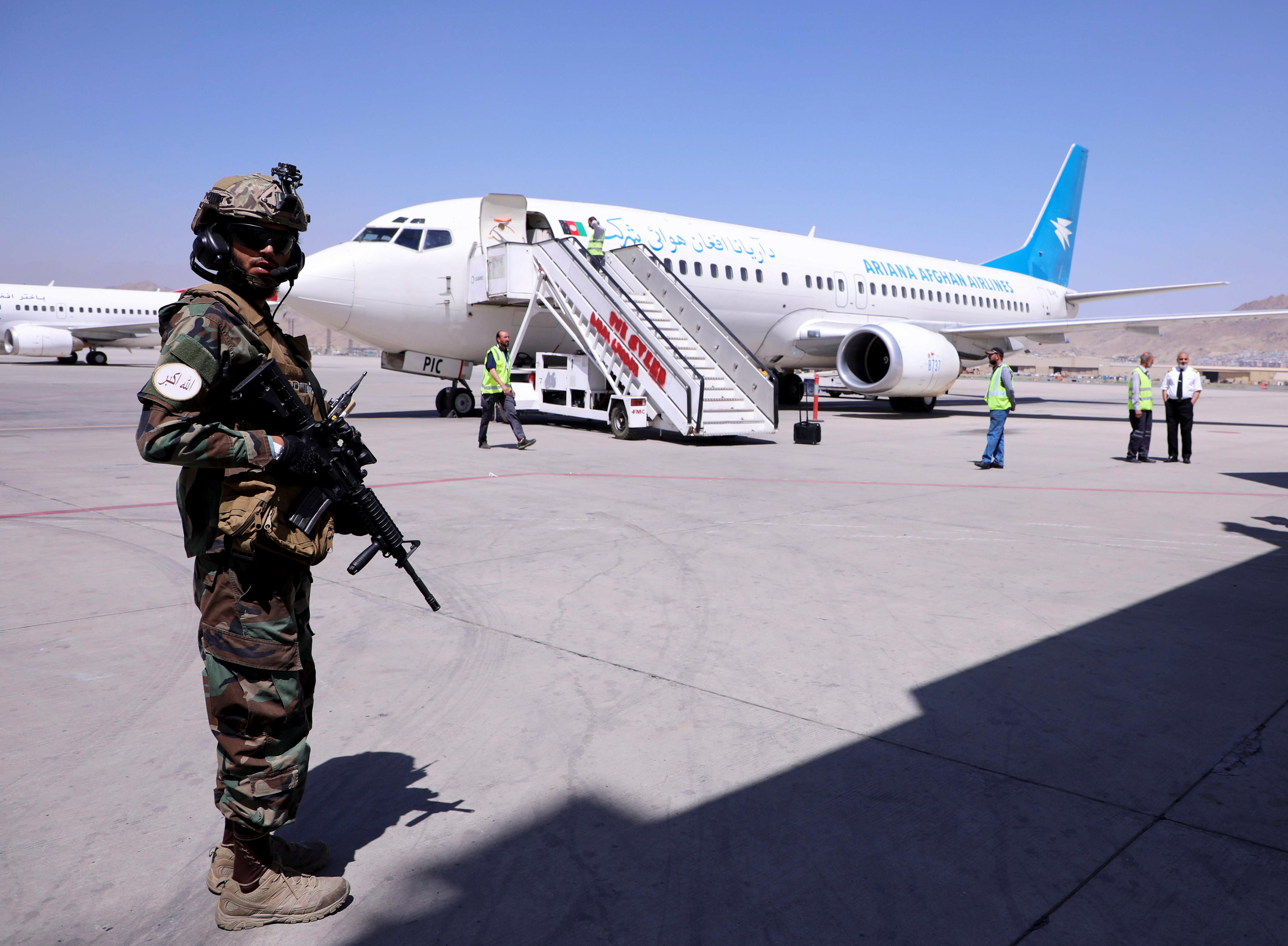 A member of Taliban forces stands guard next to a plane that has arrived from Kandahar at Hamid Karzai International Airport in Kabul, Afghanistan September 5, 2021. REUTERS/Stringer