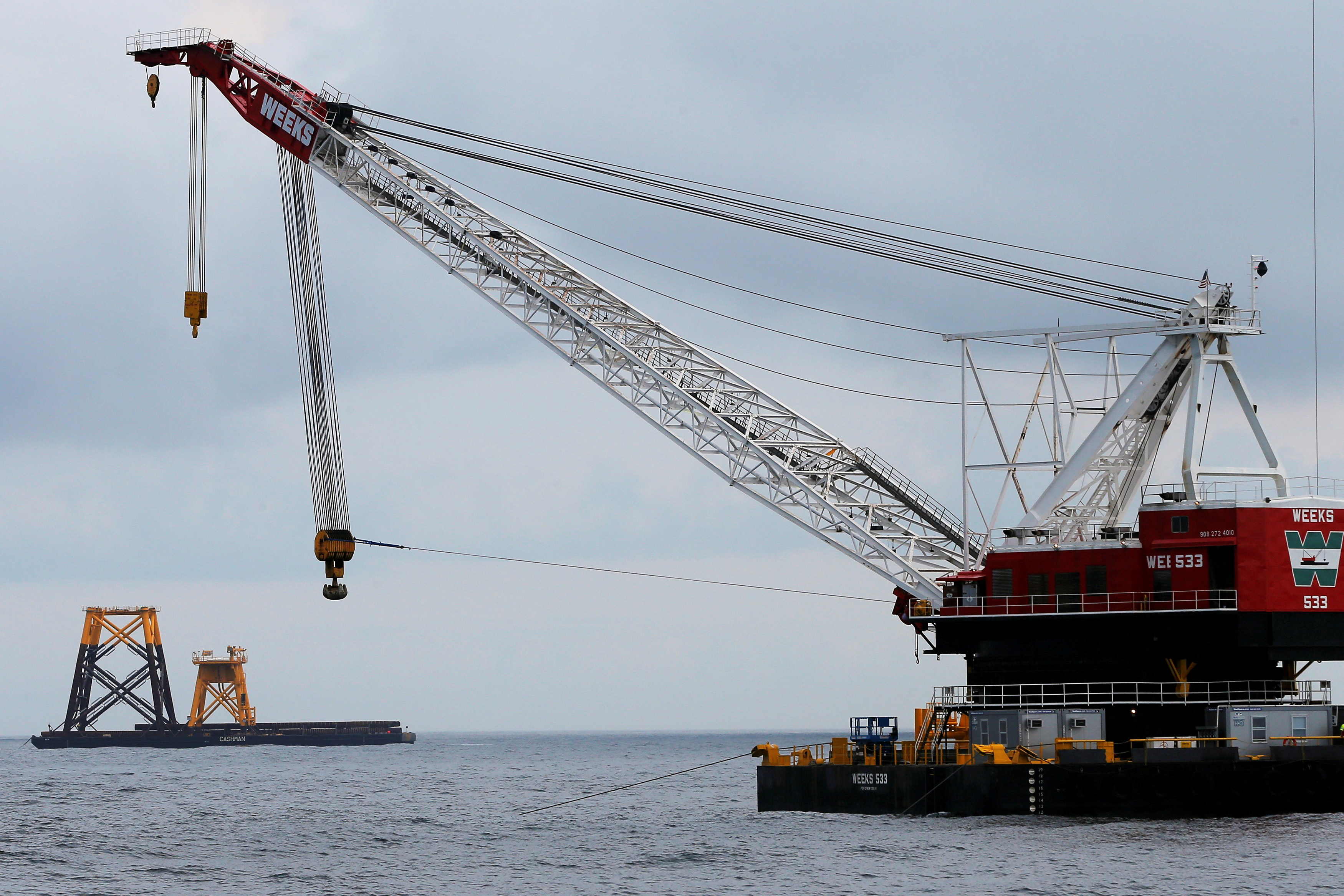 A construction crane floats next to a barge carrying jacket support structures and a platform for a turbine for a wind farm in the waters of the Atlantic Ocean off Block Island, Rhode Island July 27, 2015. REUTERS/Brian Snyder