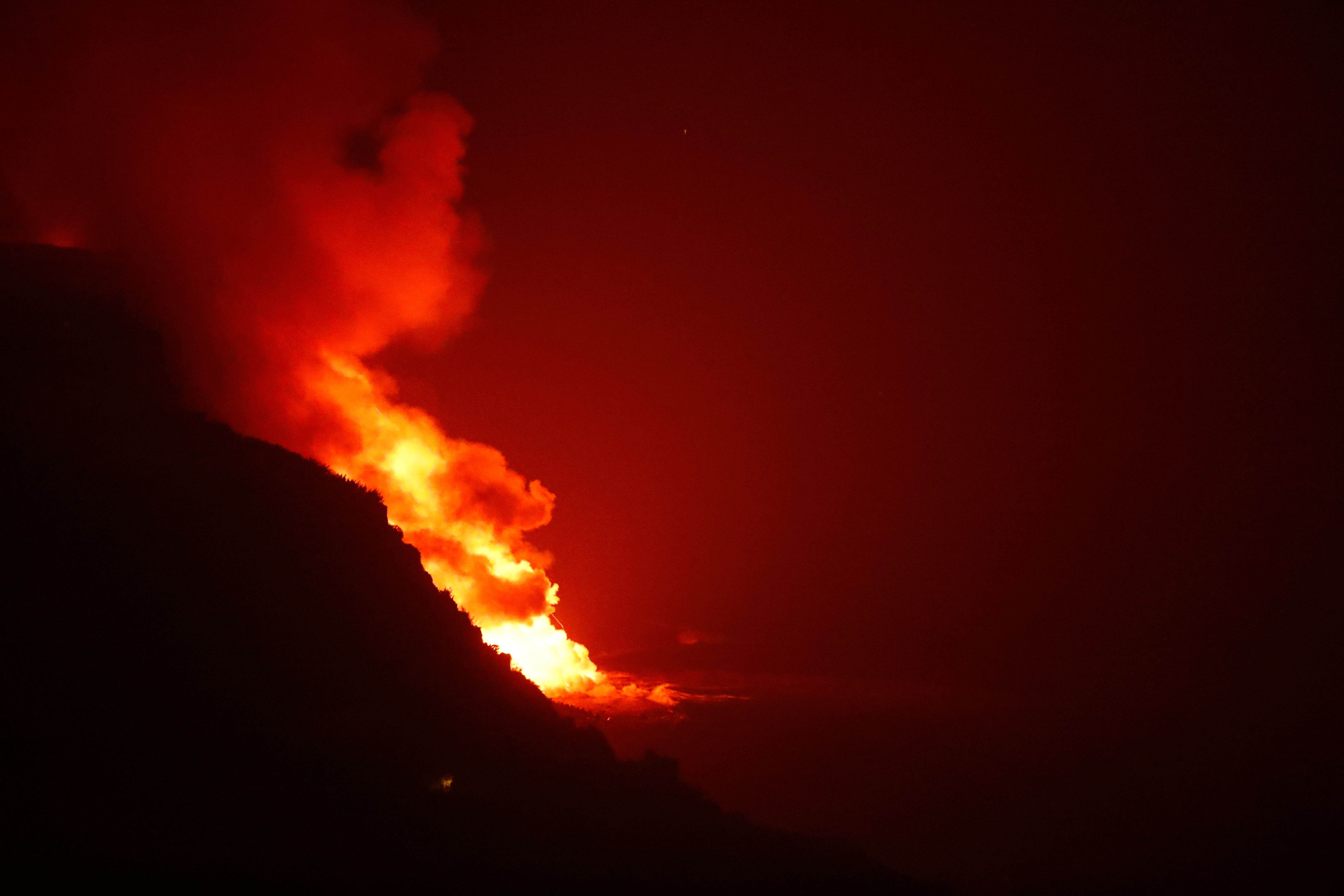 Lava flows into the sea, as seen from Tijarafe, following the eruption of a volcano on the Canary Island of La Palma, Spain, September 28, 2021. REUTERS/Borja Suarez