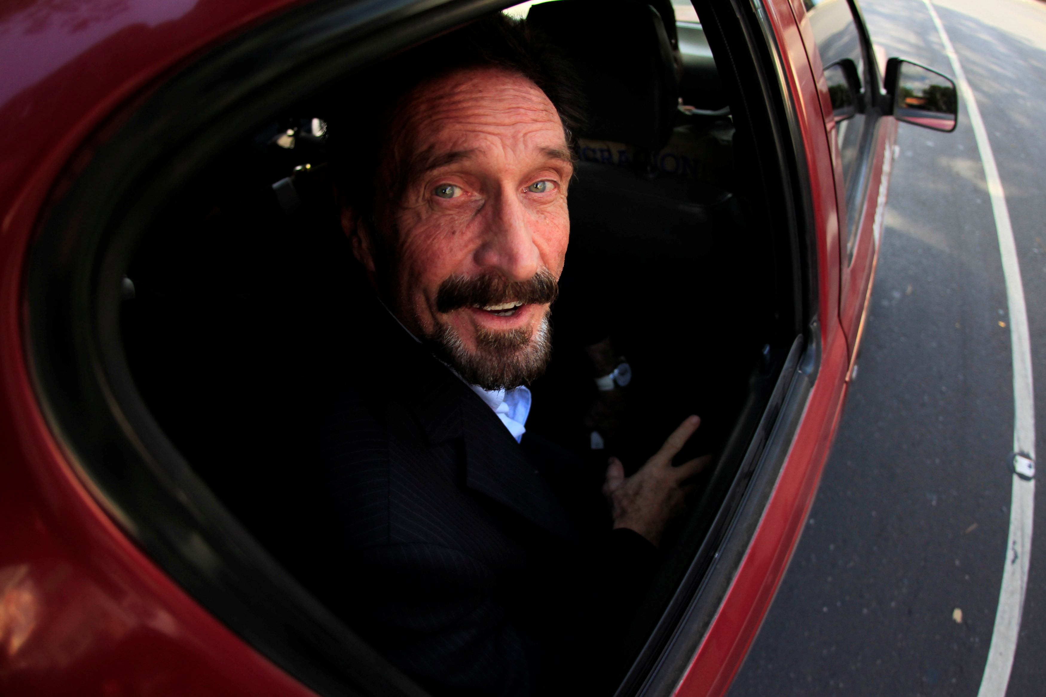Software pioneer John McAfee is escorted by immigration officers to the Guatemalan Airport in Guatemala City December 12, 2012.  REUTERS/Jorge Dan Lopez/File Photo