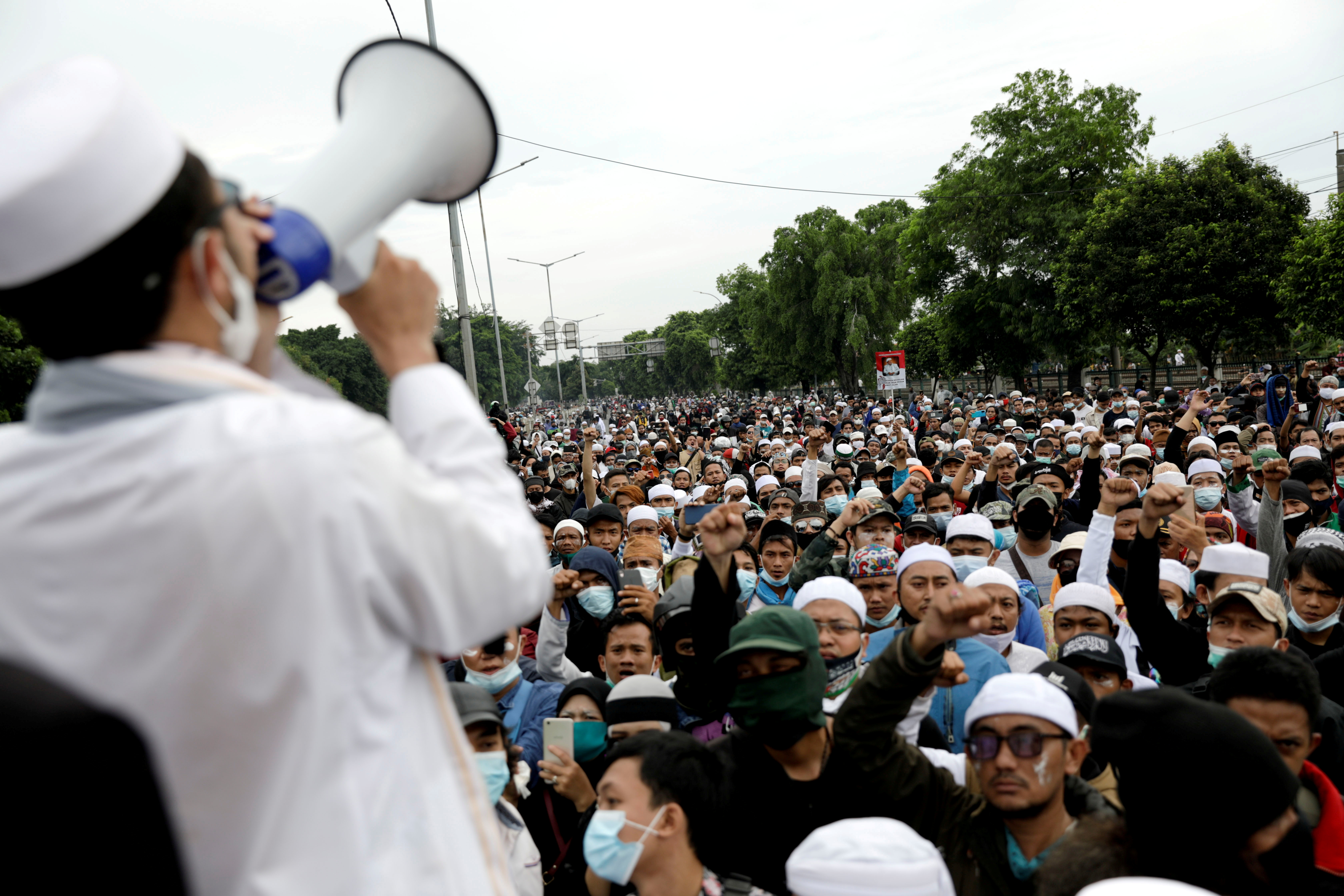 People gather during a protest supporting Rizieq Shihab, an Indonesian Islamic cleric who is sentenced for breaching coronavirus disease (COVID-19) curbs after his return last year from self-imposed exile, in Jakarta, Indonesia, June 24, 2021. REUTERS/Willy Kurniawan
