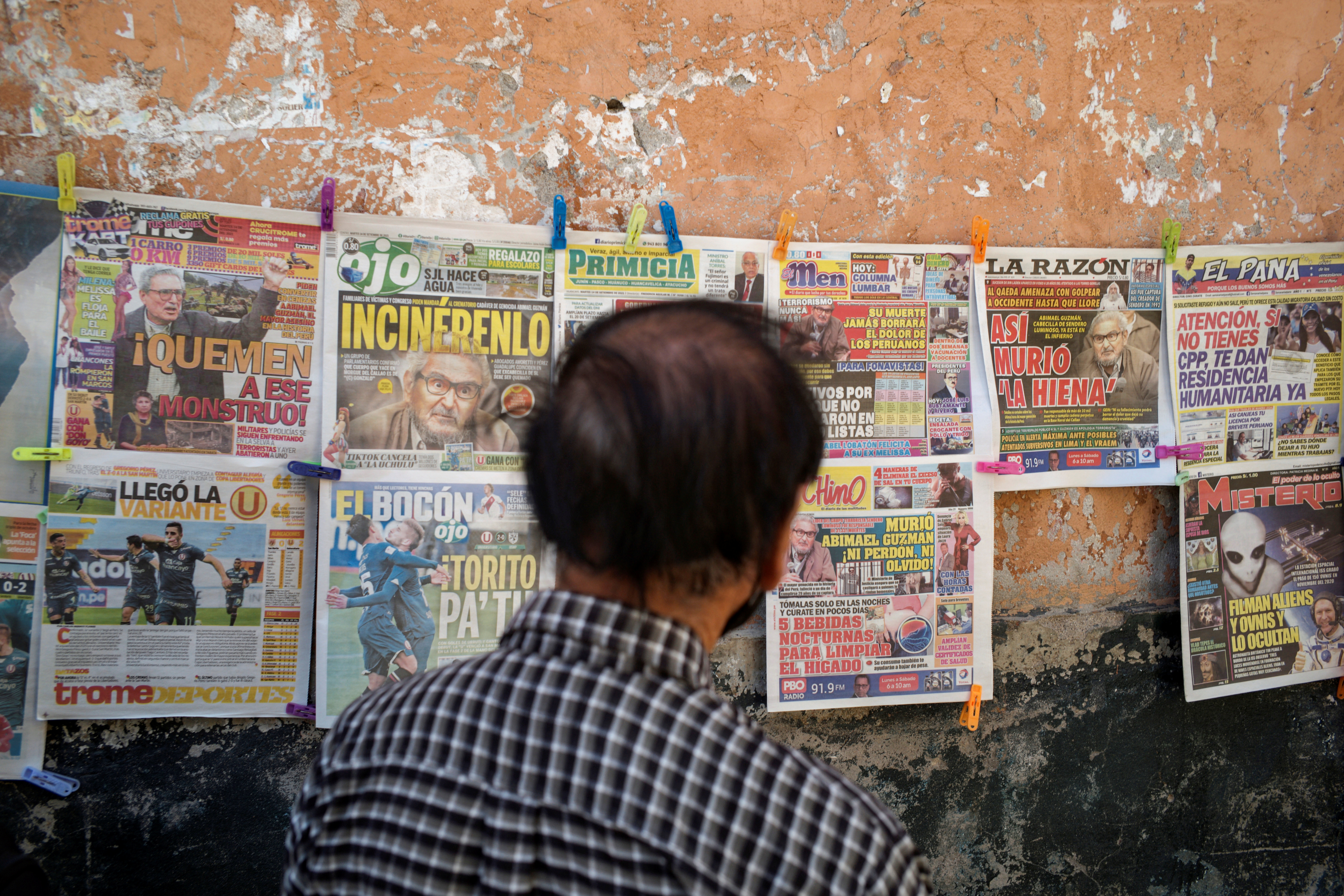 A man looks at newspapers reporting on the death of Abimael Guzman, founder of the Peruvian guerrilla group Shining Path, in Ayacucho, Peru September 14, 2021. REUTERS/Alessandro Cinque