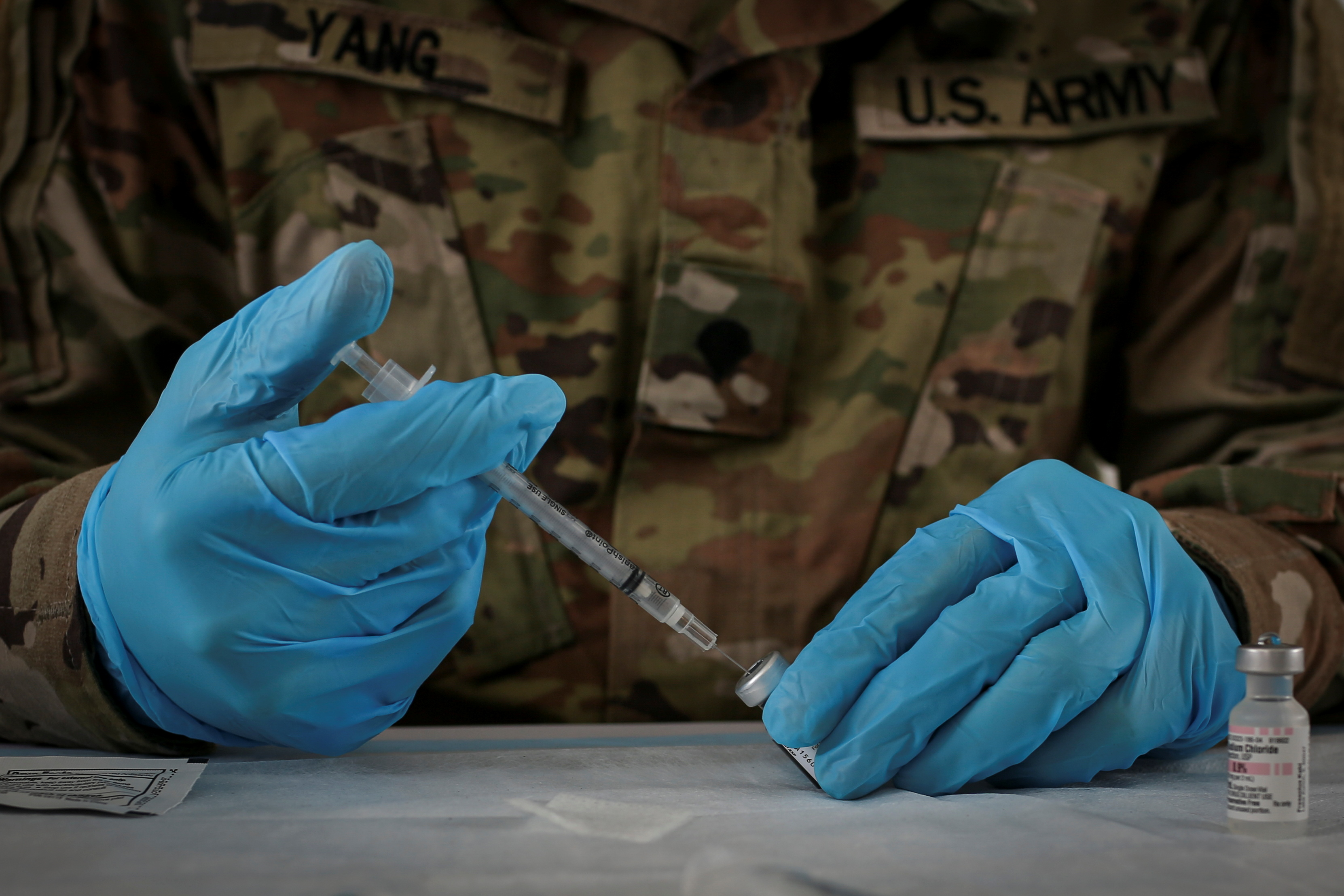 A U.S. Army soldier from the 2nd Armored Brigade Combat Team, 1st Infantry Division, prepares Pfizer coronavirus disease (COVID-19) vaccines to inoculate people in a mass vaccination site supported by the federal government at the Miami Dade College North Campus in Miami, Florida, U.S., March 10, 2021. REUTERS/Marco Bello