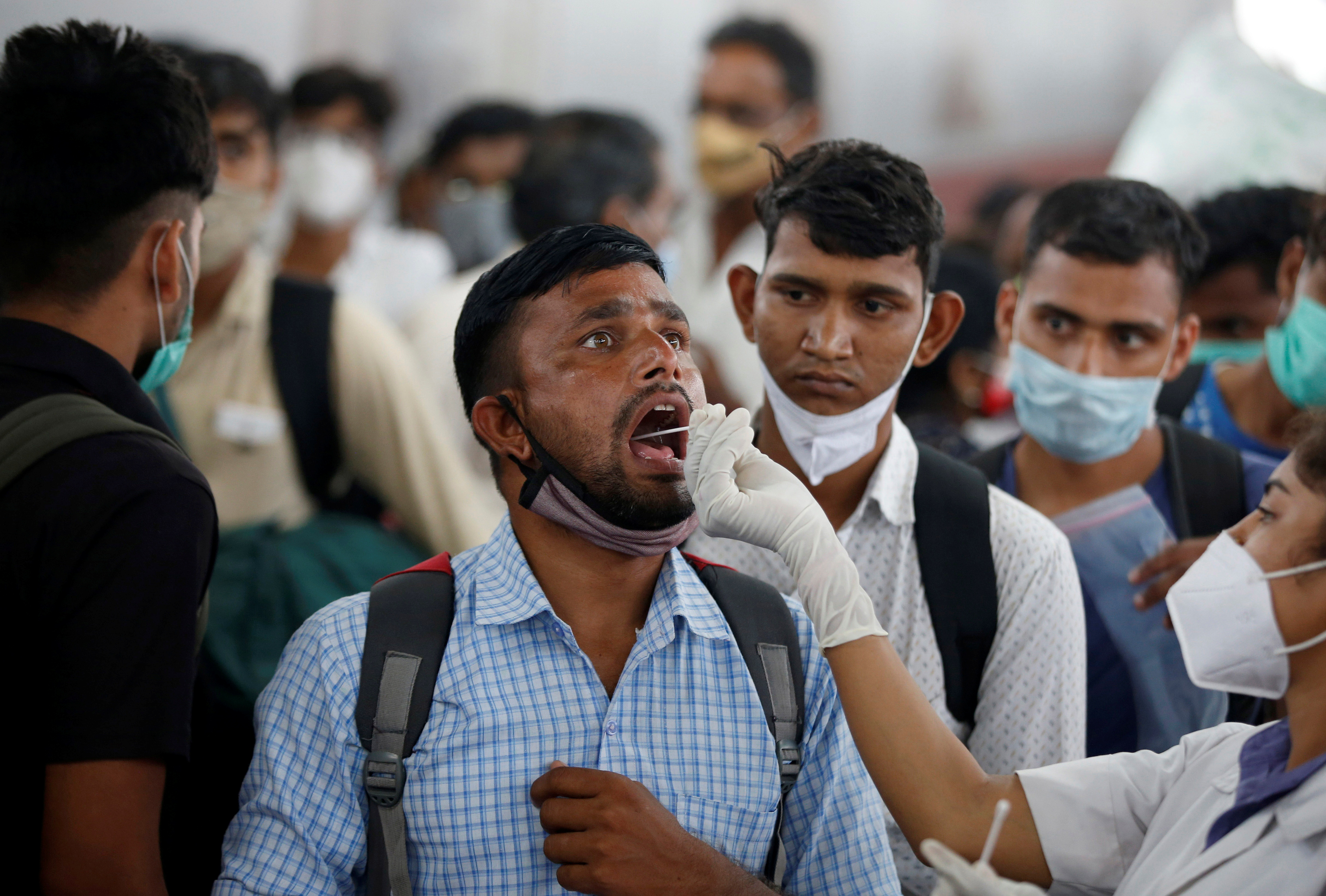 A healthcare worker collects swab from a man for a RT-PCR test after he arrived at a railway station during the ongoing coronavirus disease (COVID-19) outbreak,  in Ahmedabad, India, September 2, 2021. REUTERS/Amit Dave