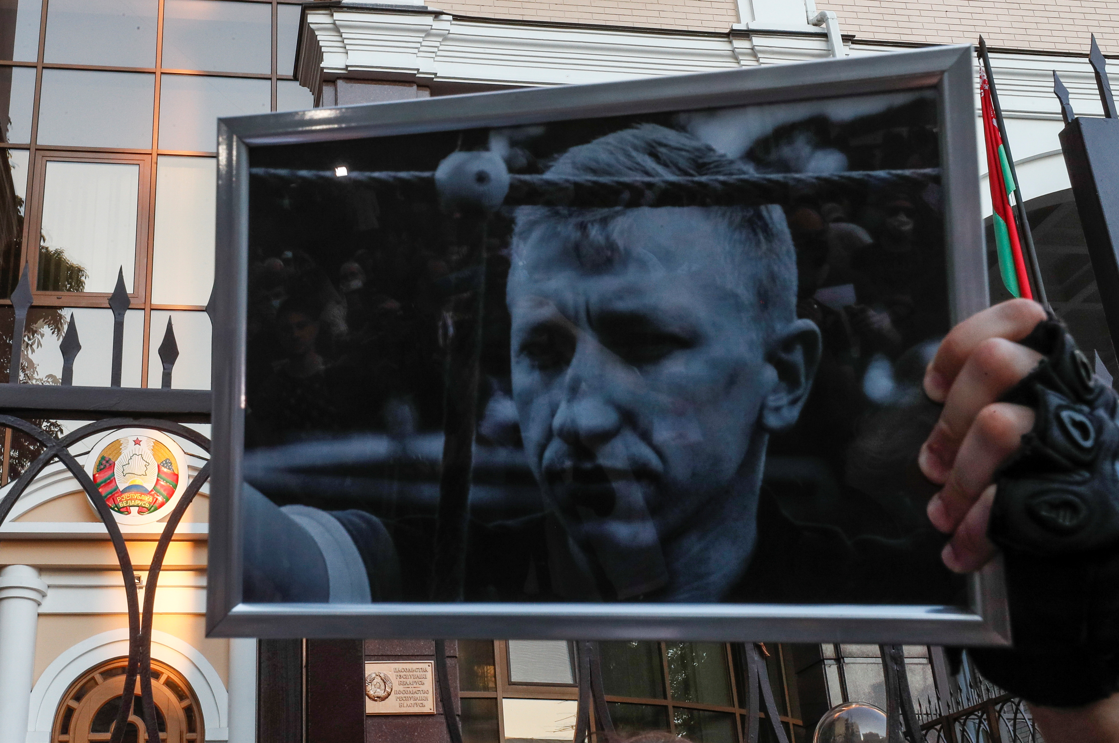 An activist holds a portrait of Vitaly Shishov during a rally to commemorate the Belarusian activist living in exile who was found hanged in a park near his home this morning, outside the Belarusian Embassy in Kyiv, Ukraine August 3, 2021. REUTERS/Gleb Garanich