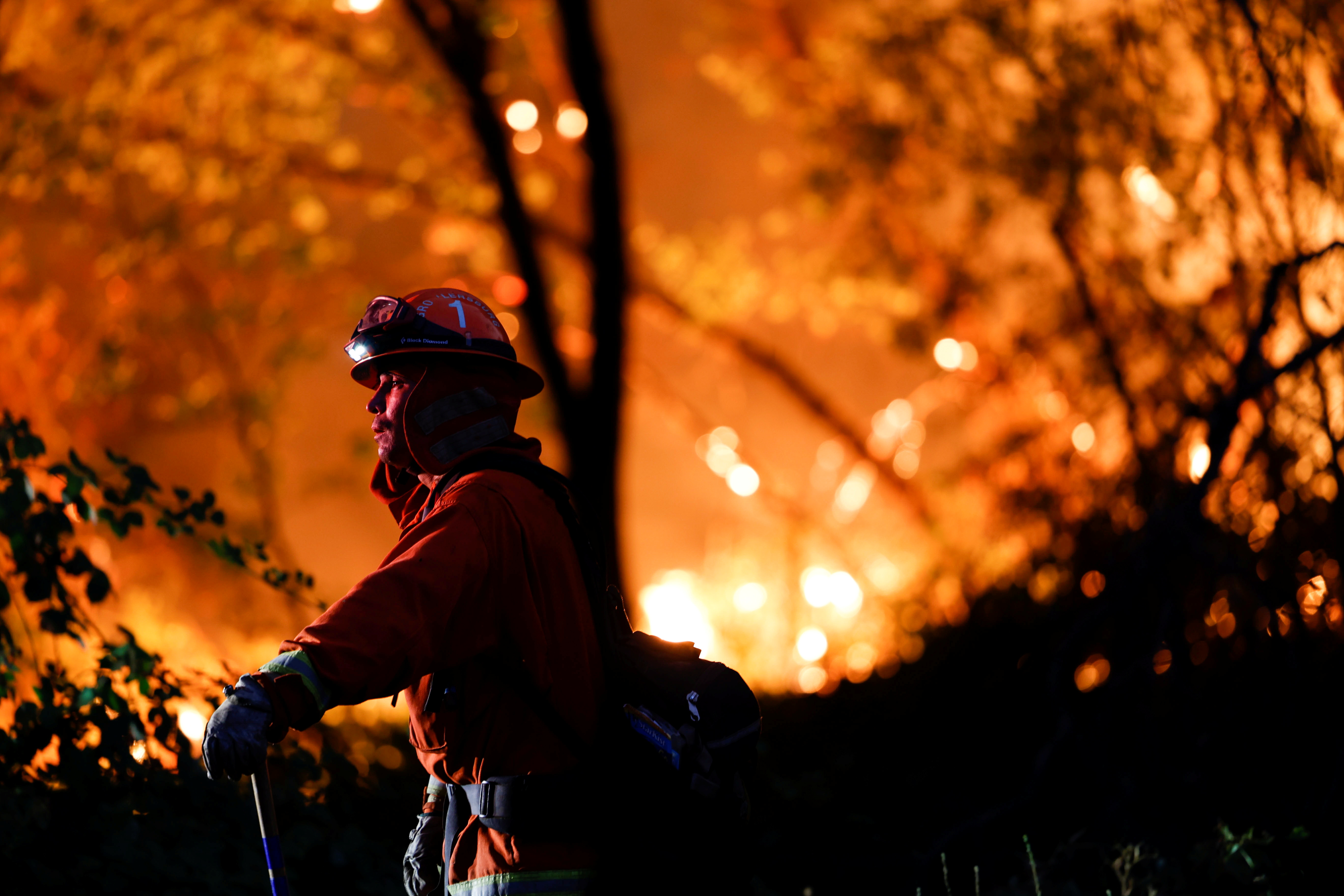 A firefighter monitors flames which were threatening homes by the River Fire, a wildfire near the Placer County town of Grass Valley, California, U.S., August 4, 2021. REUTERS/Fred Greaves