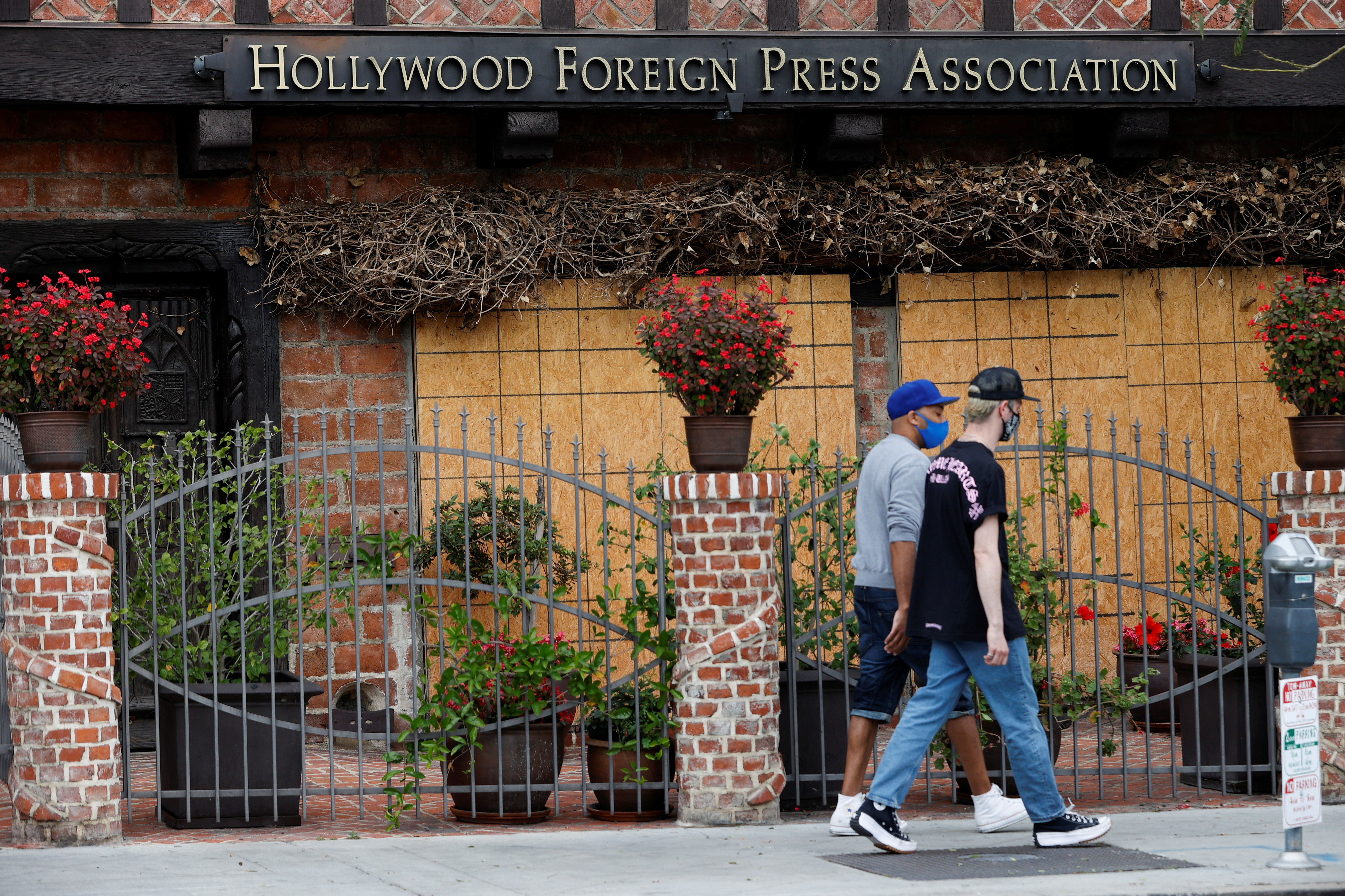 People walk past the Hollywood Foreign Press Association (HFPA) headquarters, in West Hollywood, California, U.S., May 10, 2021. REUTERS/Mario Anzuoni