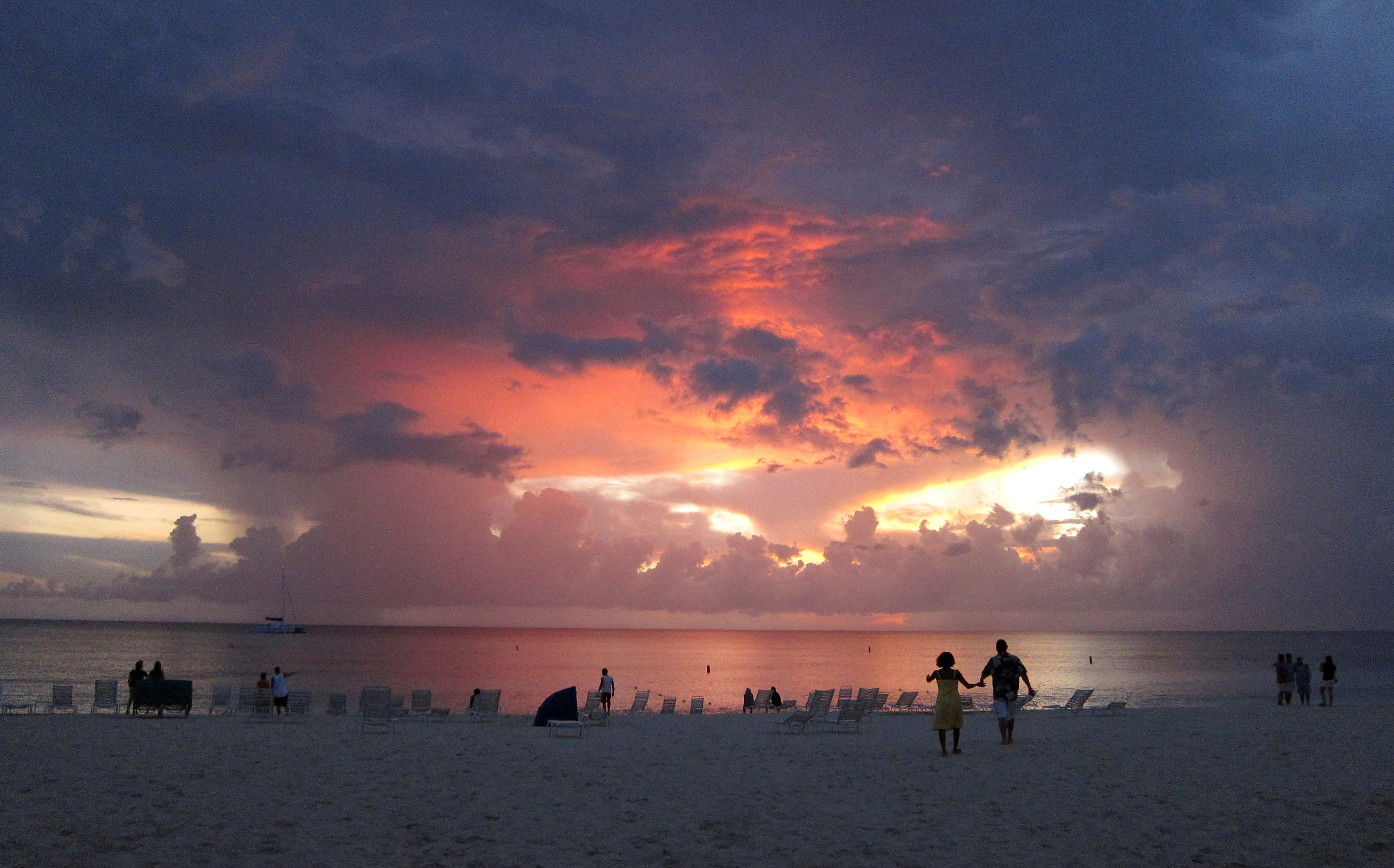 Tourists walk on Seven Mile Beach at sunset in George Town, Cayman Islands July 28, 2011. REUTERS/Gary Hershorn