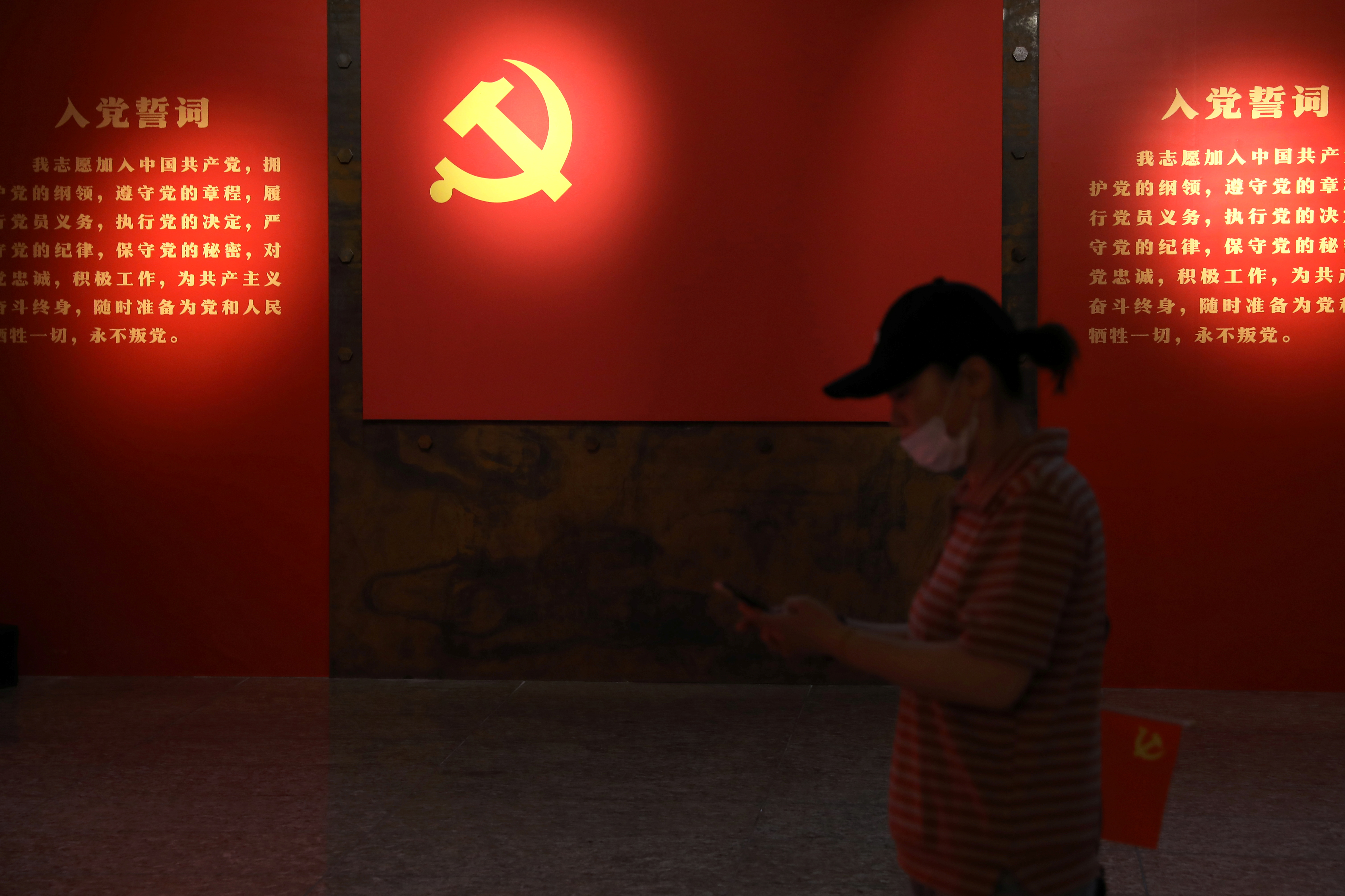 A visitor walks past a board with an emblem of the Communist Party of China at an exhibition marking the 100th anniversary of the founding of the Party, in Beijing, China June 22, 2021. Picture taken June 22, 2021. REUTERS/Tingshu Wang