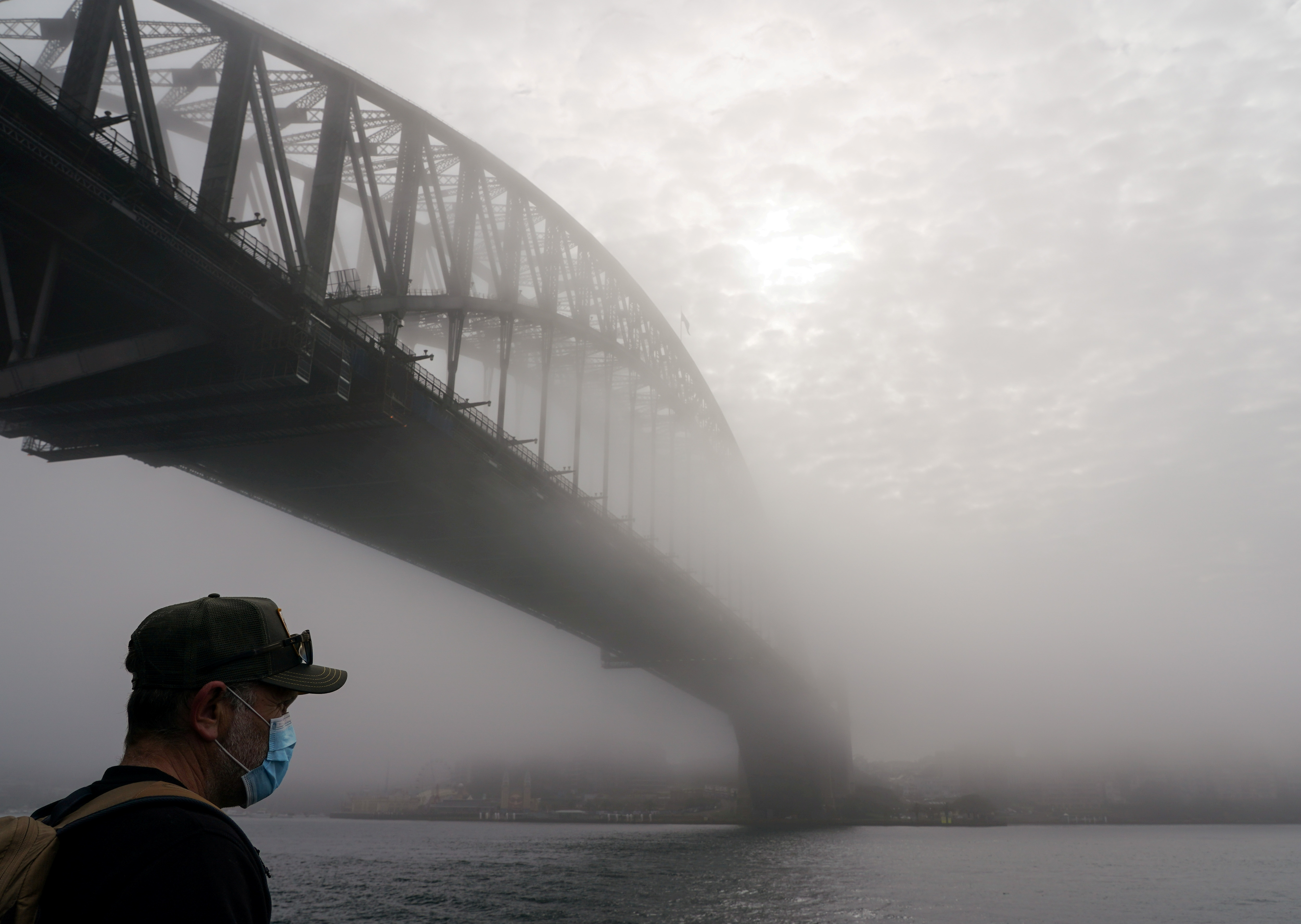 A man wearing a protective face mask takes in the waterfront view under the Sydney Harbour Bridge, seen shrouded in morning fog, during a lockdown to curb the spread of a coronavirus disease (COVID-19) outbreak in Sydney, Australia, July 1, 2021. REUTERS/Loren Elliott/File Photo