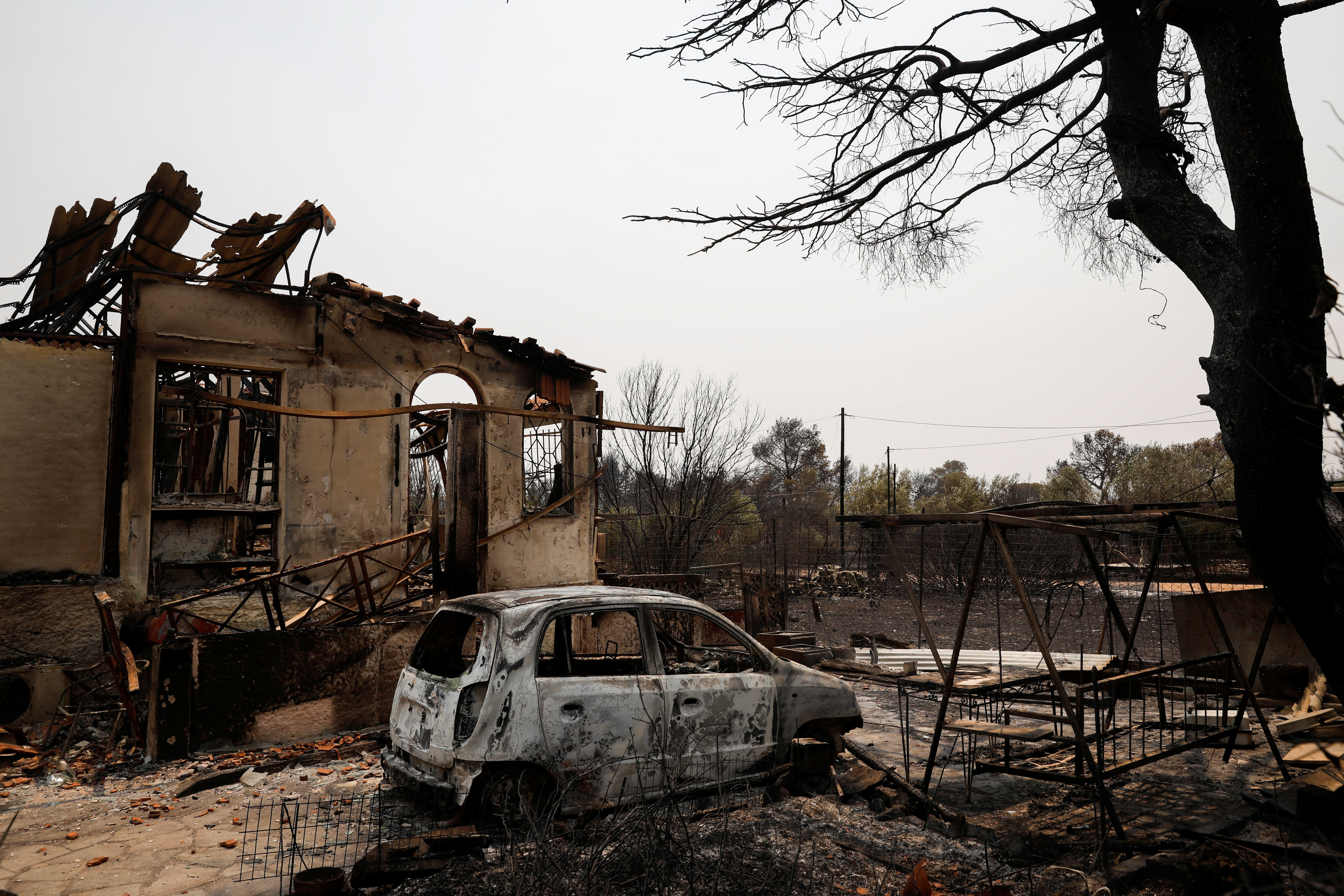 A burnt house and a car are seen following a wildfire in Varympompi suburb, north of Athens, Greece, August 4, 2021. REUTERS/Costas Baltas