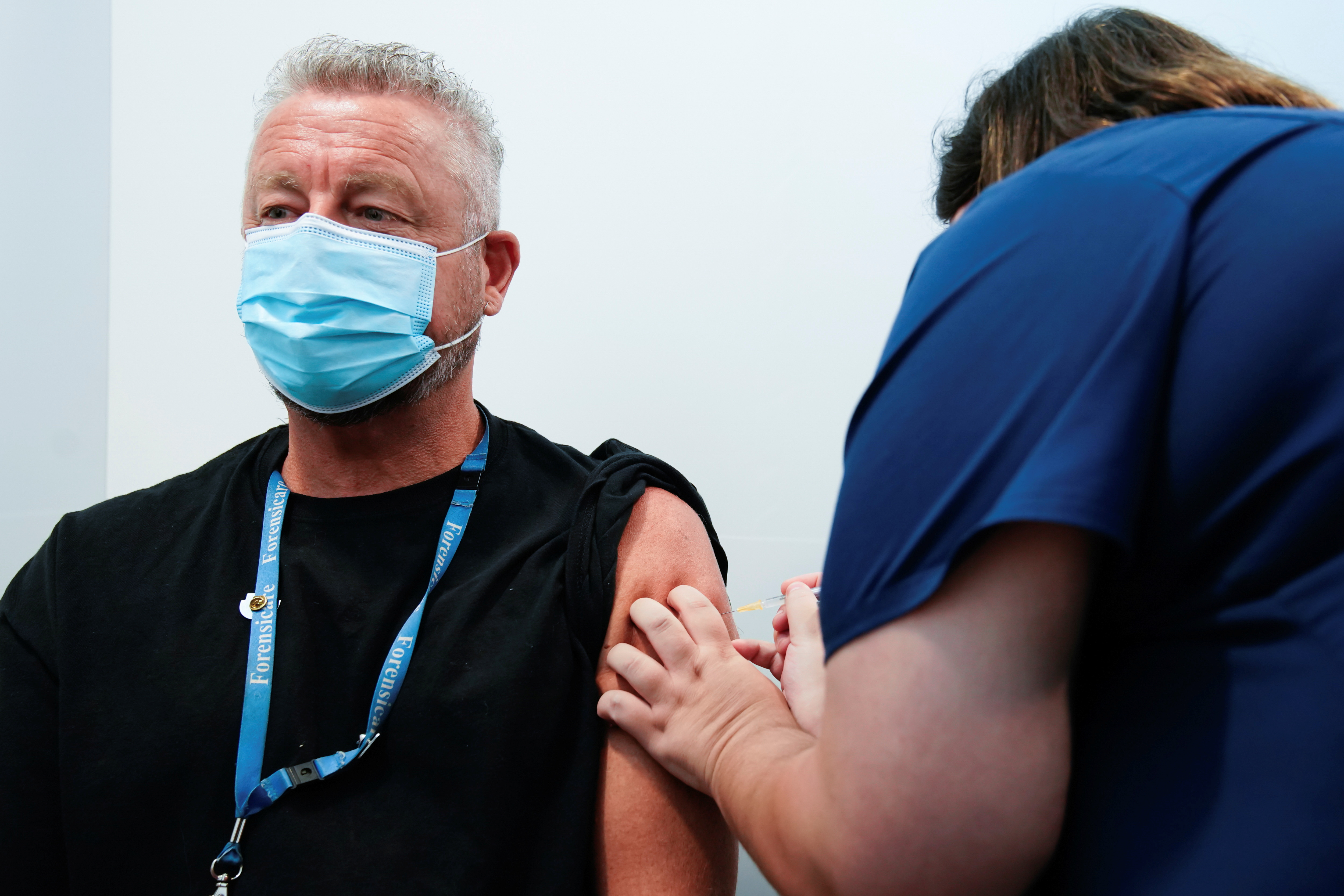 A healthcare professional administers a dose of the Pfizer coronavirus disease (COVID-19) vaccine to Dr Chris Quinn as high-risk workers receive the first vaccines in the state of Victoria's rollout of the program, in Melbourne, Australia, February 22, 2021.  REUTERS/Sandra Sanders