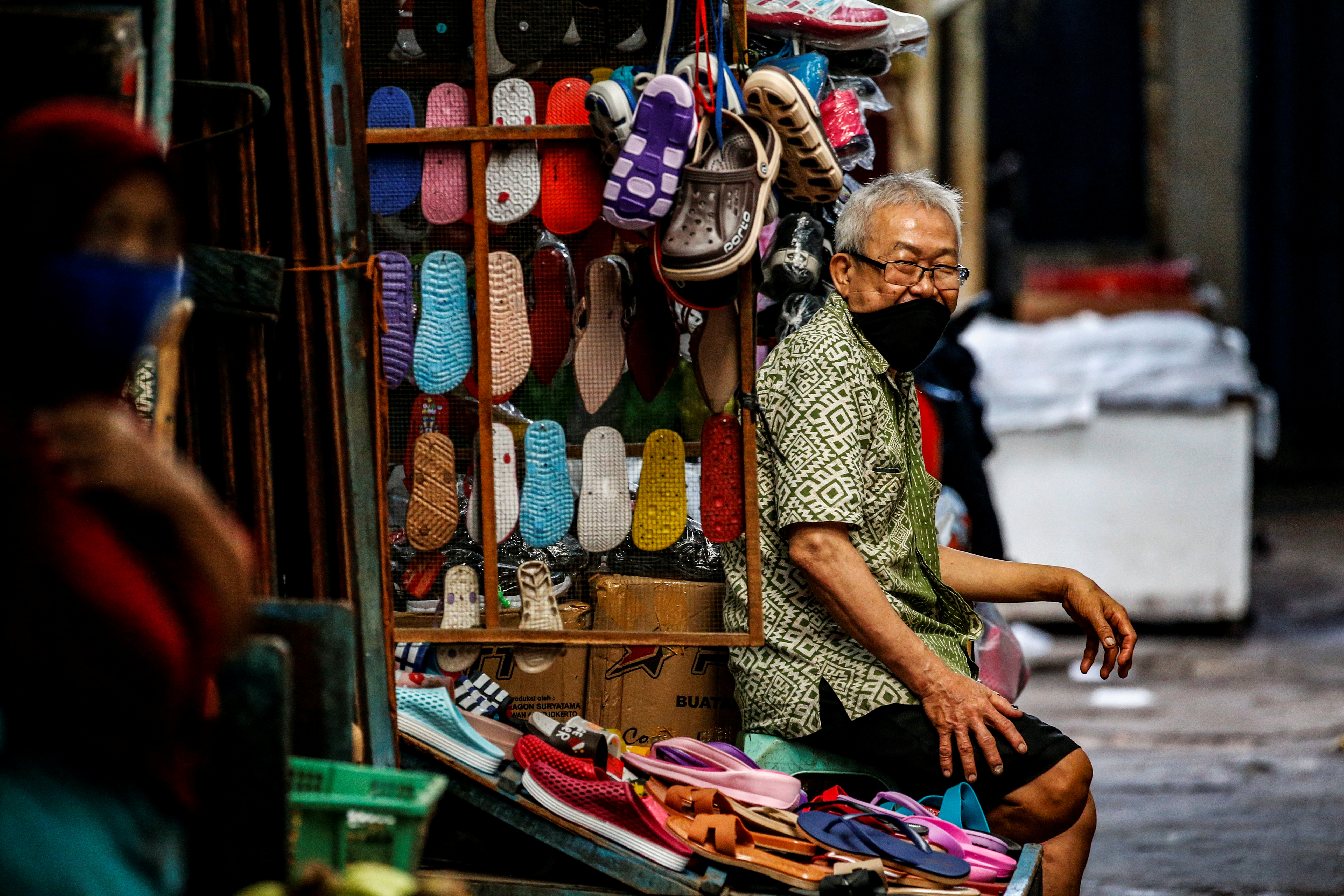A footwear vendor wears a face mask as a preventive measure against the coronavirus disease (COVID-19) at a traditional market in Jakarta, Indonesia, June 25, 2020.