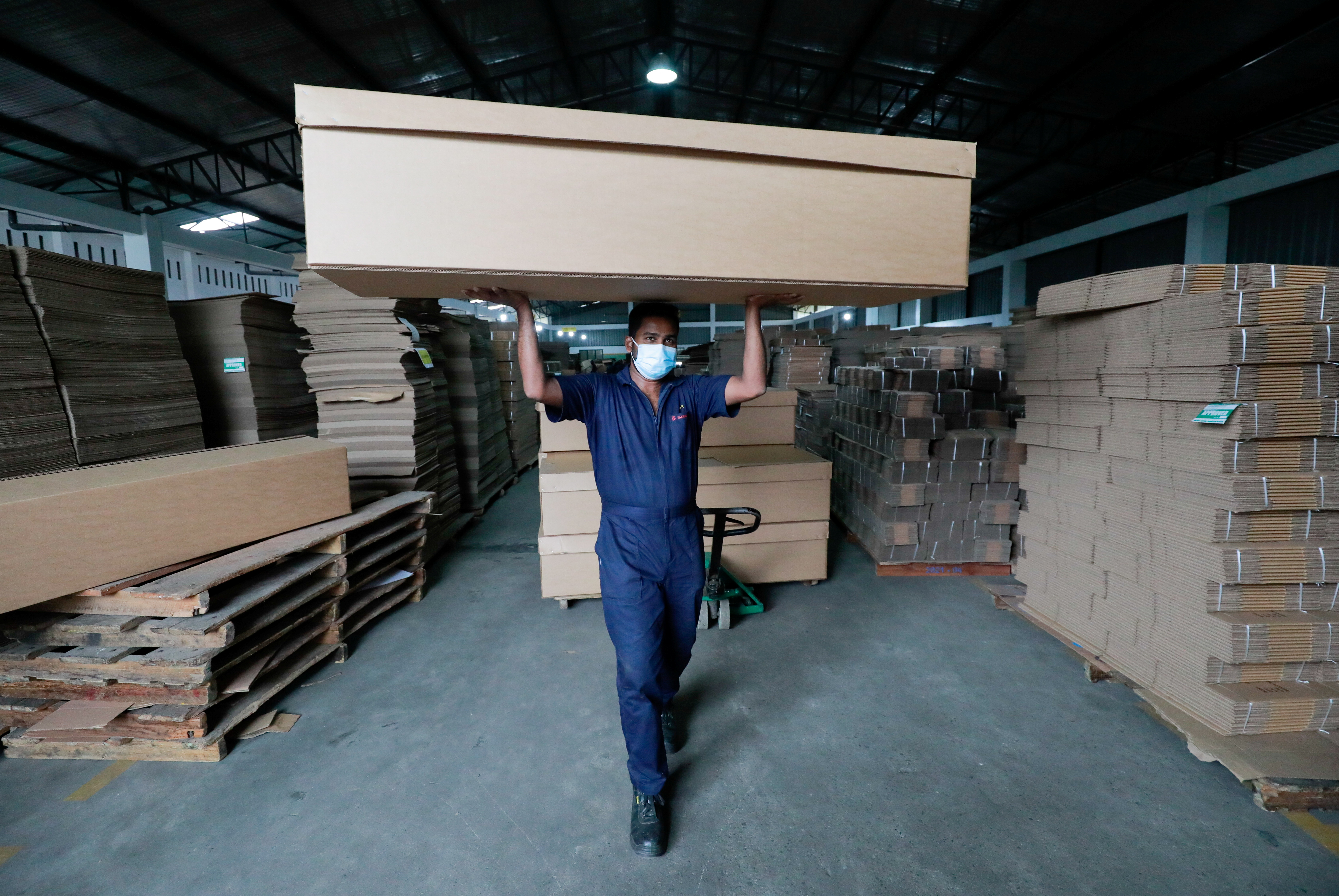 A worker carries a cardboard coffin to a truck at a factory, amid the coronavirus disease (COVID-19) pandemic, on the outskirts of Colombo, Sri Lanka August 7, 2021. Picture taken August 7, 2021. REUTERS/Dinuka Liyanawatte