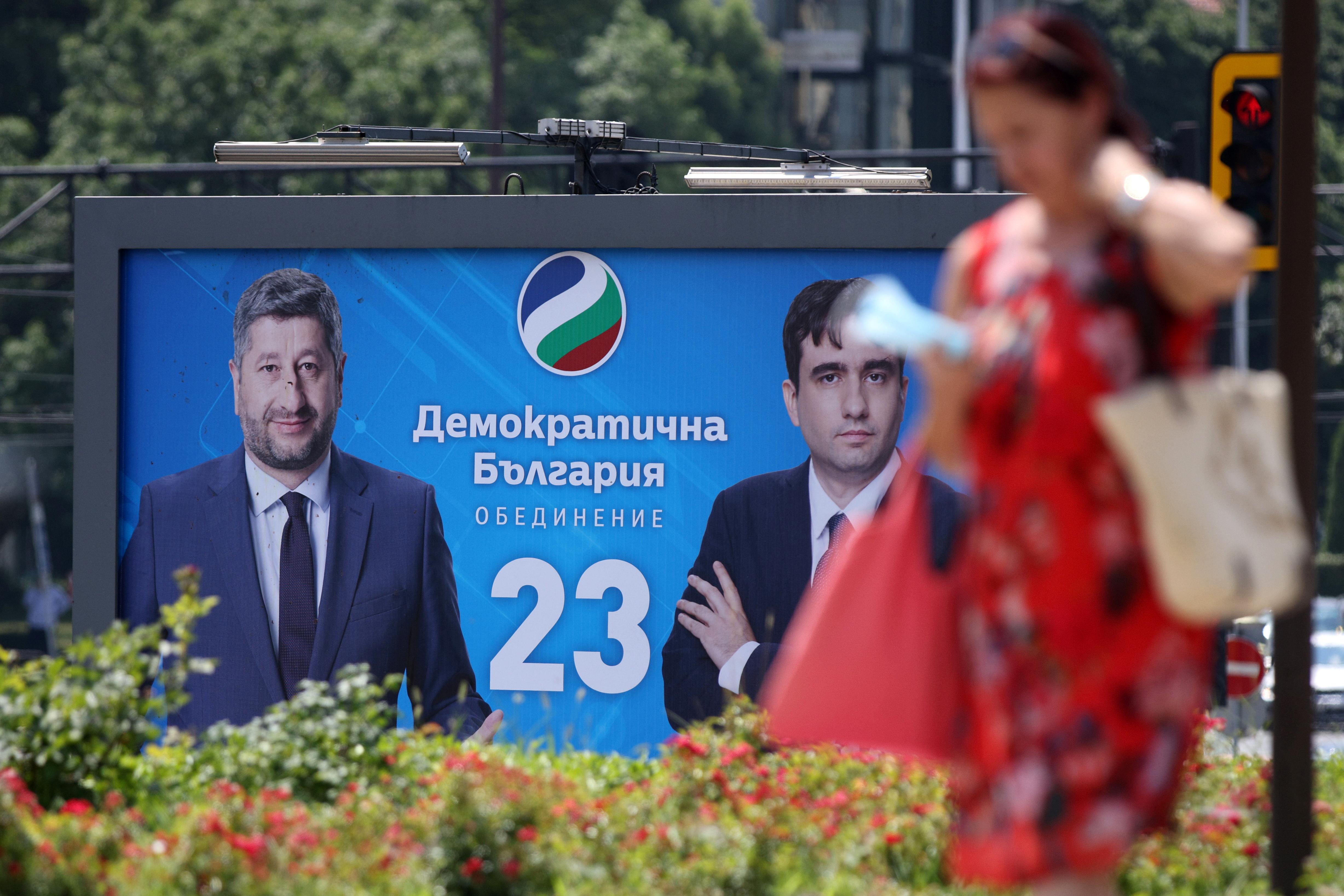A woman walks past election billboard of Democratic Bulgaria party in Sofia, Bulgaria, July 8, 2021.  REUTERS/Stoyan Nenov