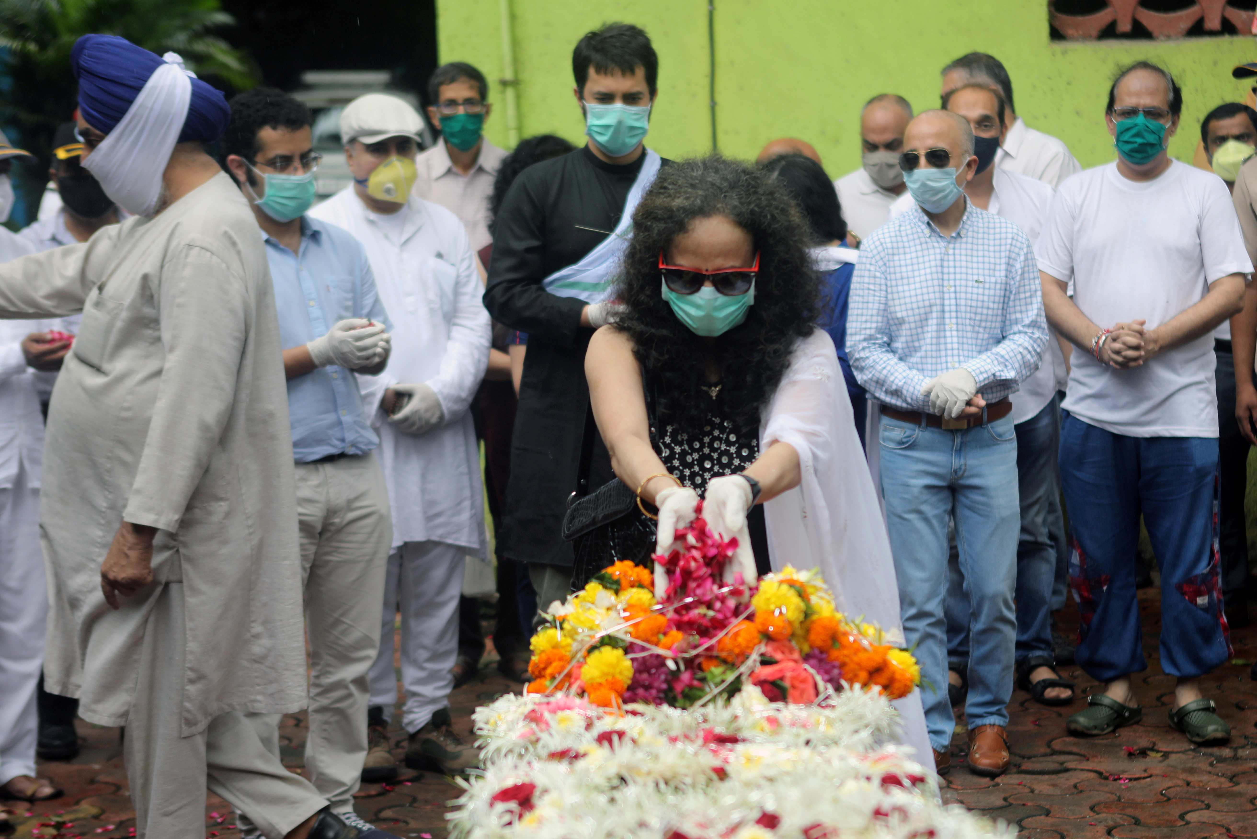 Wife of deceased Air India pilot Deepak Sathe places flowers on his coffin during his funeral in Mumbai, India, August 11, 2020. REUTERS/Francis Mascarenhas/File Photo